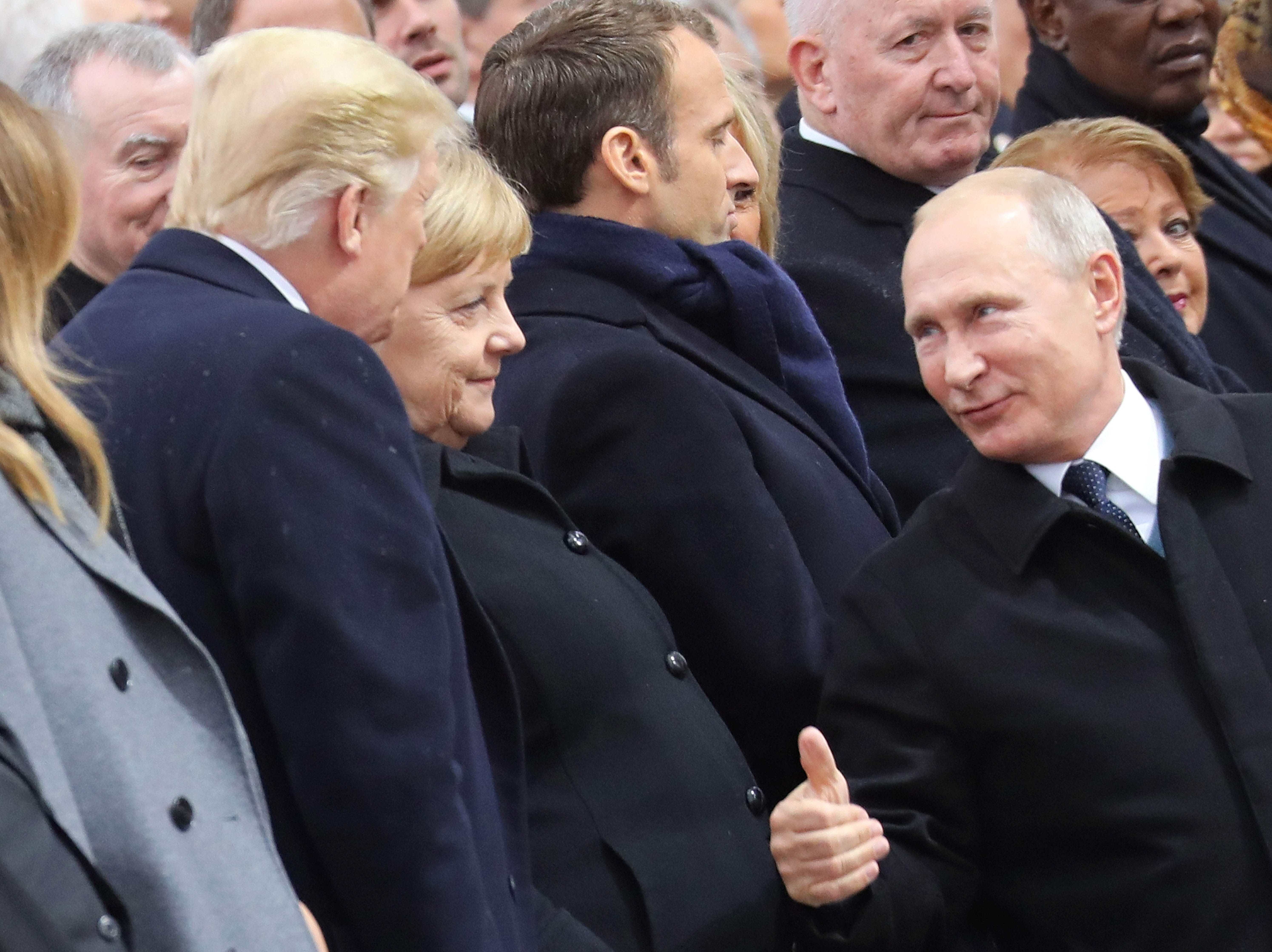 Russian President Vladimir Putin, right, talks with German Chancellor Angela Merkel, center,  and US President Donald Trump as they attend a ceremony at the Arc de Triomphe in Paris on Nov. 11, 2018 as part of commemorations marking the 100th anniversary of the November 11, 1918 armistice, ending World War I.