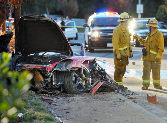 Firefighters work next to the charred remains of the crashed Porsche Carrera GT in which Paul Walker and friend Roger Rodas died on Nov. 30, 2013.