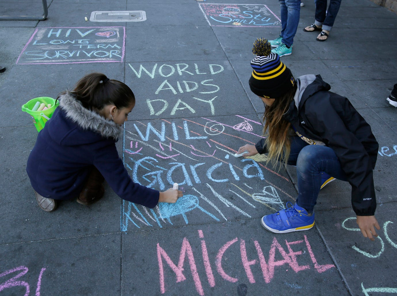 Serenity Rico, left, and Jalayah Francisco, right, 5th graders from the Harvey Milk Civil Rights Academy, use chalk to write the names of those who have died from AIDS on the sidewalk of Castro Street on Dec. 1, 2015, in San Francisco. The event was called Inscribe on World AIDS Day.