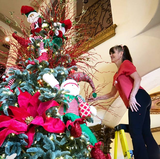 Christmas decorating expert Kim Scribner putting the finishing touches on a tree topper in Dallas, Texas.