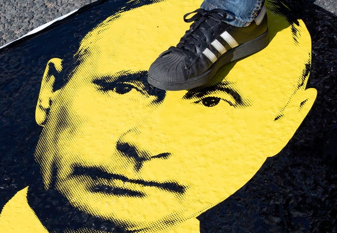 A man steps on a portrait of Russian President Vladimir Putin during an opposition rally in Moscow on July 29, 2018.