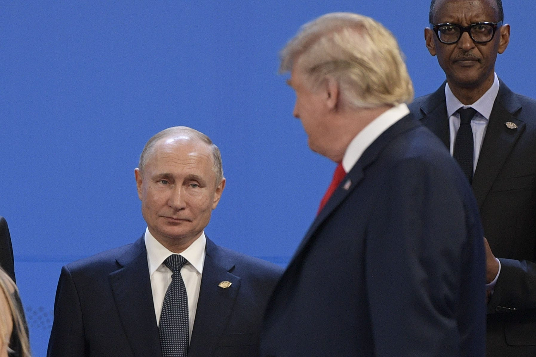 President Donald Trump, right, looks at Russia's President Vladimir Putin as they take place for a family photo, during the G20 Leaders' Summit in Buenos Aires, on Nov. 30, 2018. Global leaders gather in the Argentine capital for a two-day G20 summit beginning on Friday likely to be dominated by simmering international tensions over trade.