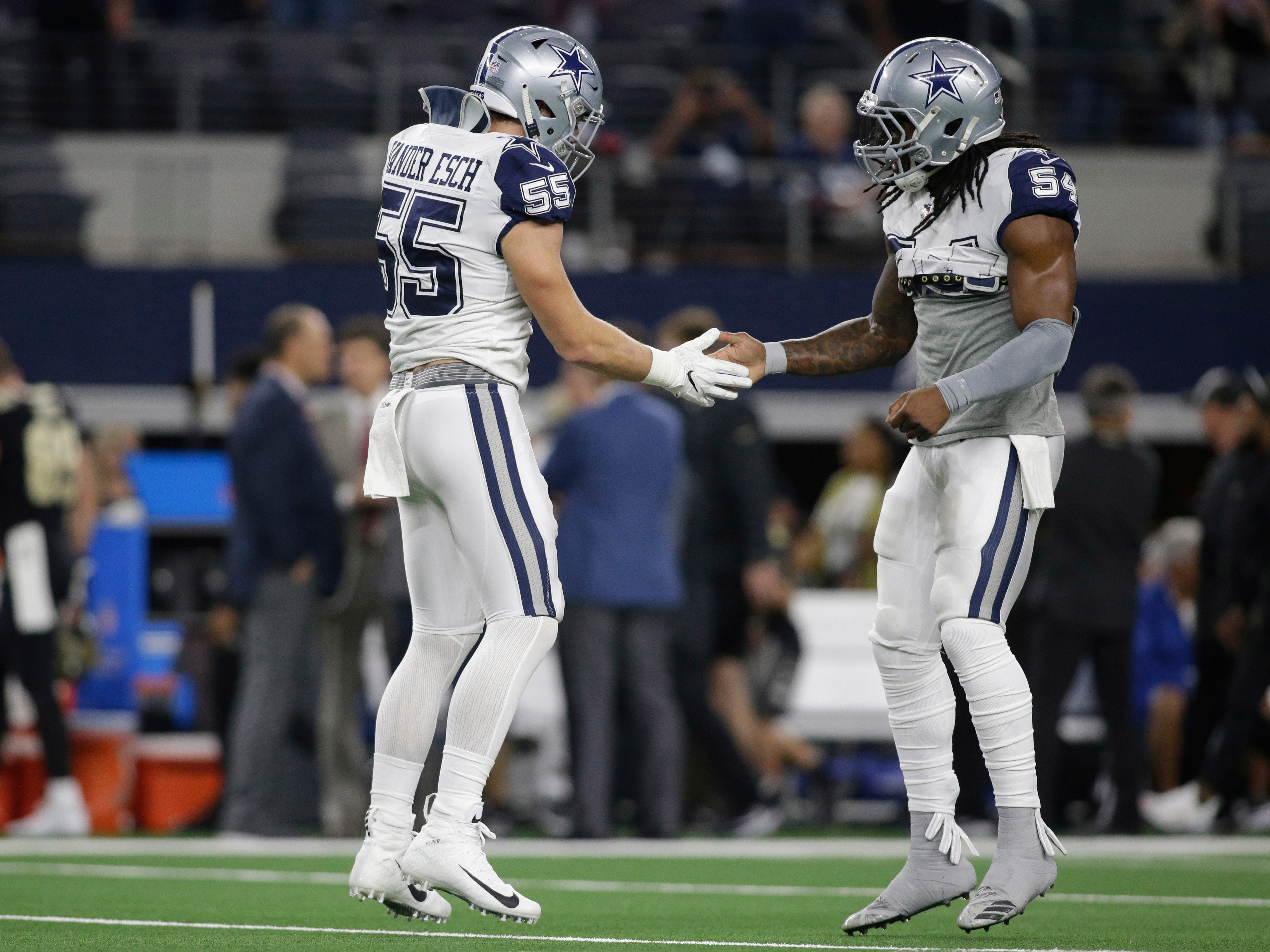 Dallas Cowboys outside linebacker Leighton Vander Esch (55) and middle linebacker Jaylon Smith (54) react on the field before the game against the New Orleans Saints at AT&T Stadium.