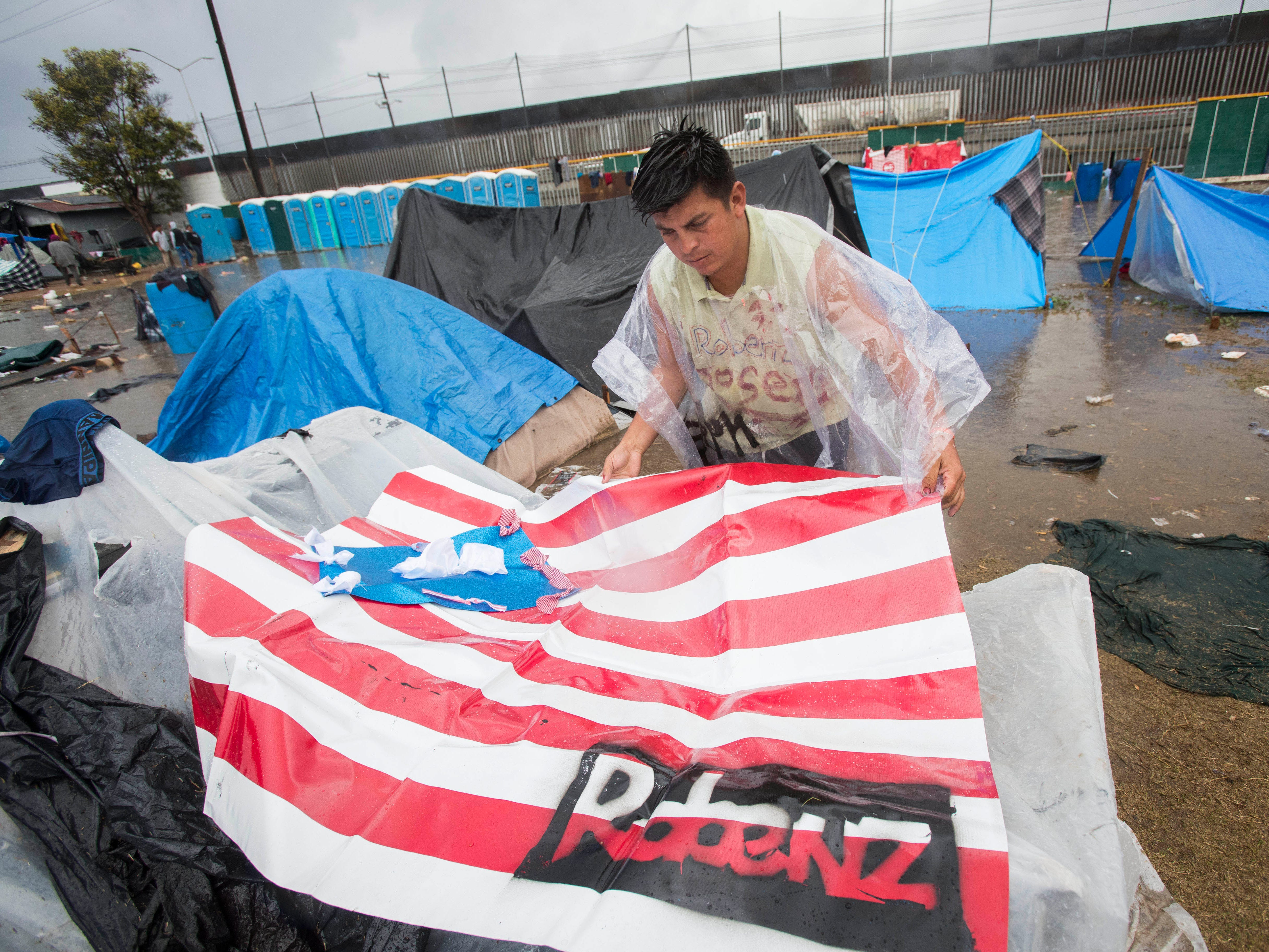 A migrant man uses a tarp to try to prevent more water from entering his tent at the  Benito Juarez sports complex in Tijuana, Mexico on Nov. 29, 2018.