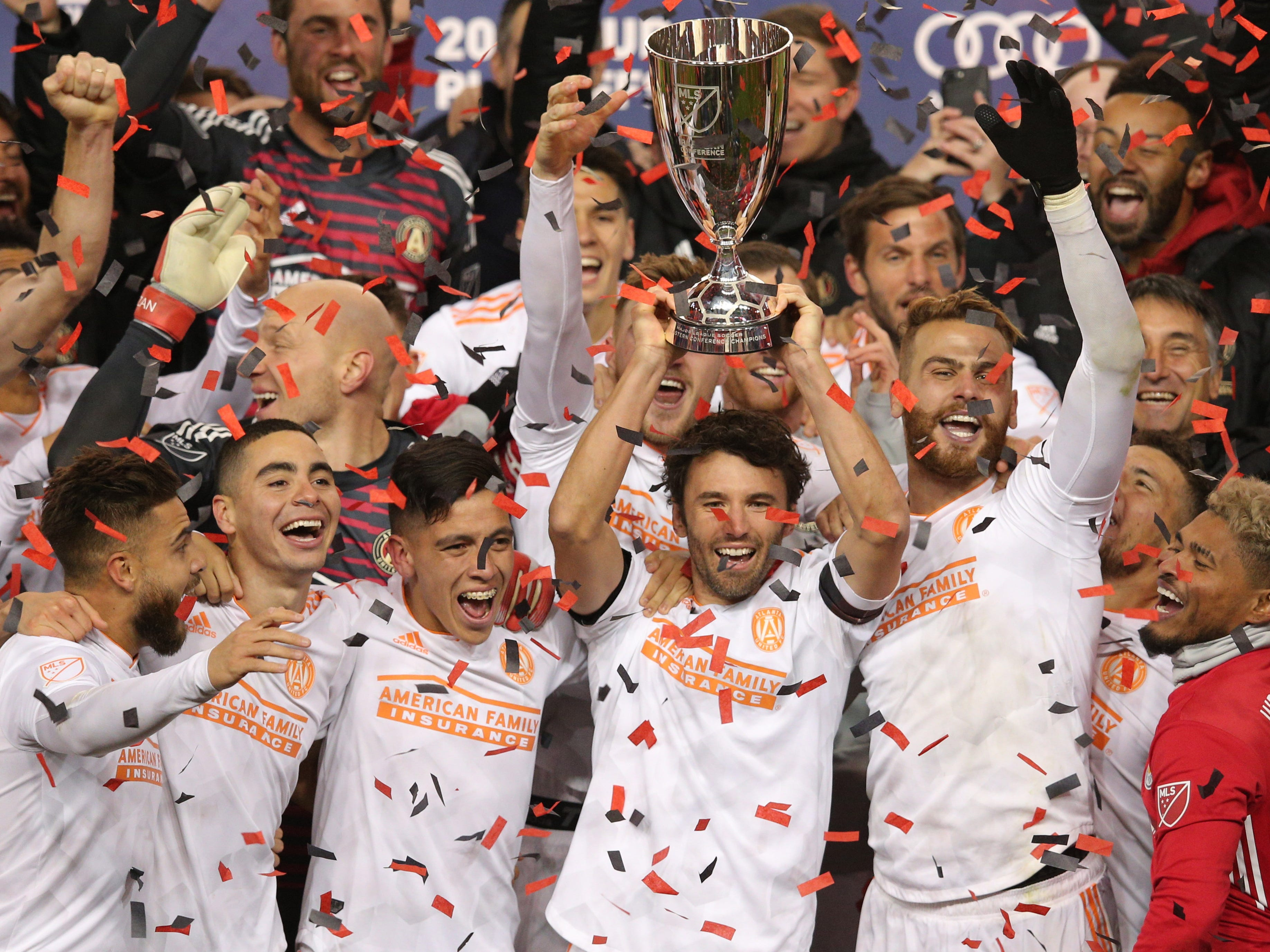 Atlanta United defender Michael Parkhurst holds up the trophy as the team celebrates after defeating the New York Red Bulls in the MLS Eastern Conference Championship at Red Bull Arena.