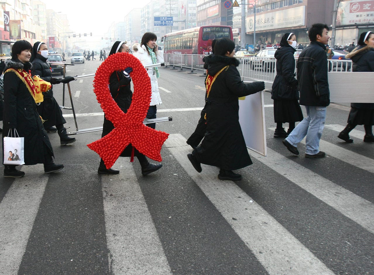A nun holding a huge red ribbon sign made by a charity organization affiliated to a local catholic church walks with volunteers during an AIDS awareness event in Shenyang, in northeast China's Liaoning province on World AIDS Day  Dec. 1, 2006. China's Health Ministry said the number of reported HIV and AIDS cases rose almost 30 percent to 183,733 in the first 10 months of this year, but health experts say actual cases are likely to be four to five times the reported figure.