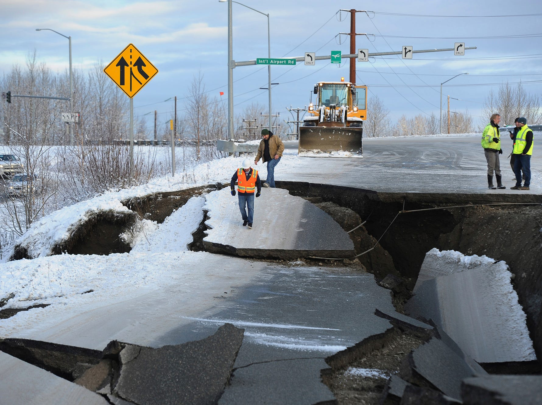 Workers inspect an off-ramp that collapsed during a morning earthquake, Friday, Nov. 30, 2018, in Anchorage, Alaska.
