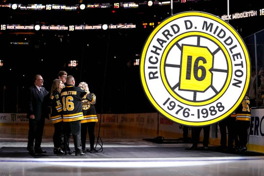 Former Boston Bruins star Rick Middleton (far left) watches as his retired number is raised to the rafters at TD Garden.