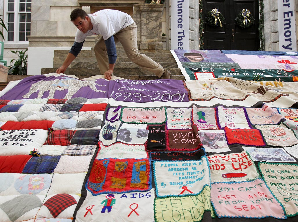 Volunteer Noah Fixelle spreads out a 12x12 ft quilt during the sixth annual World AIDS Day AIDS Memorial Quilt in the R. Dobbs University Center at Emory on  Dec.  1, 2010 in Atlanta.   With more than 1,400 quilt panels, each panel tells  the story of a single life cut short by HIV/AIDS.