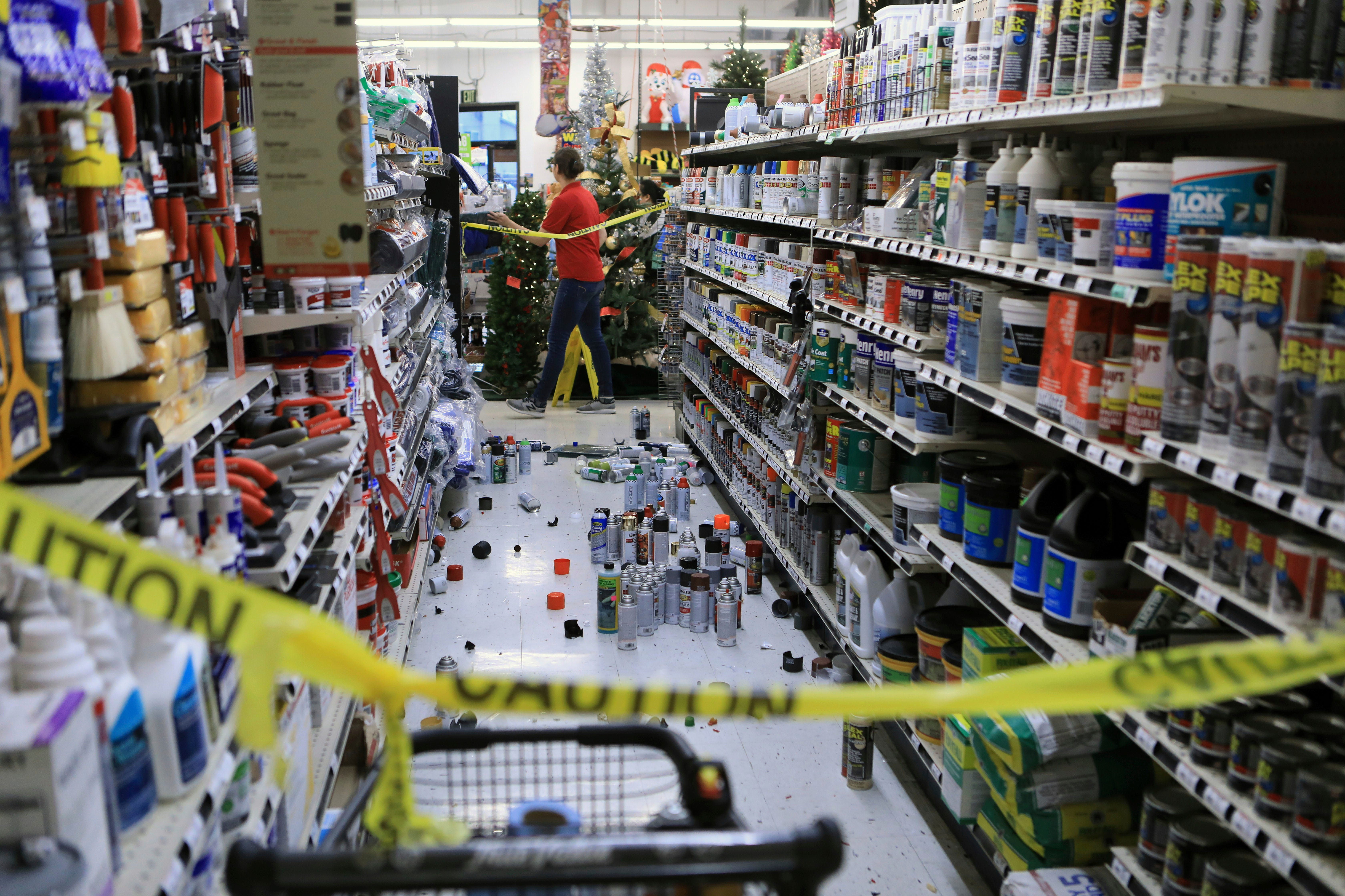 An employee walks past a damaged aisle at Anchorage True Value hardware store after an earthquake, Friday morning, Nov. 30, 2018, in Anchorage, Alaska. Tim Craig, owner of the south Anchorage store, said no one was injured but hundreds of items hit the floor and two shelves collapsed in a stock room.