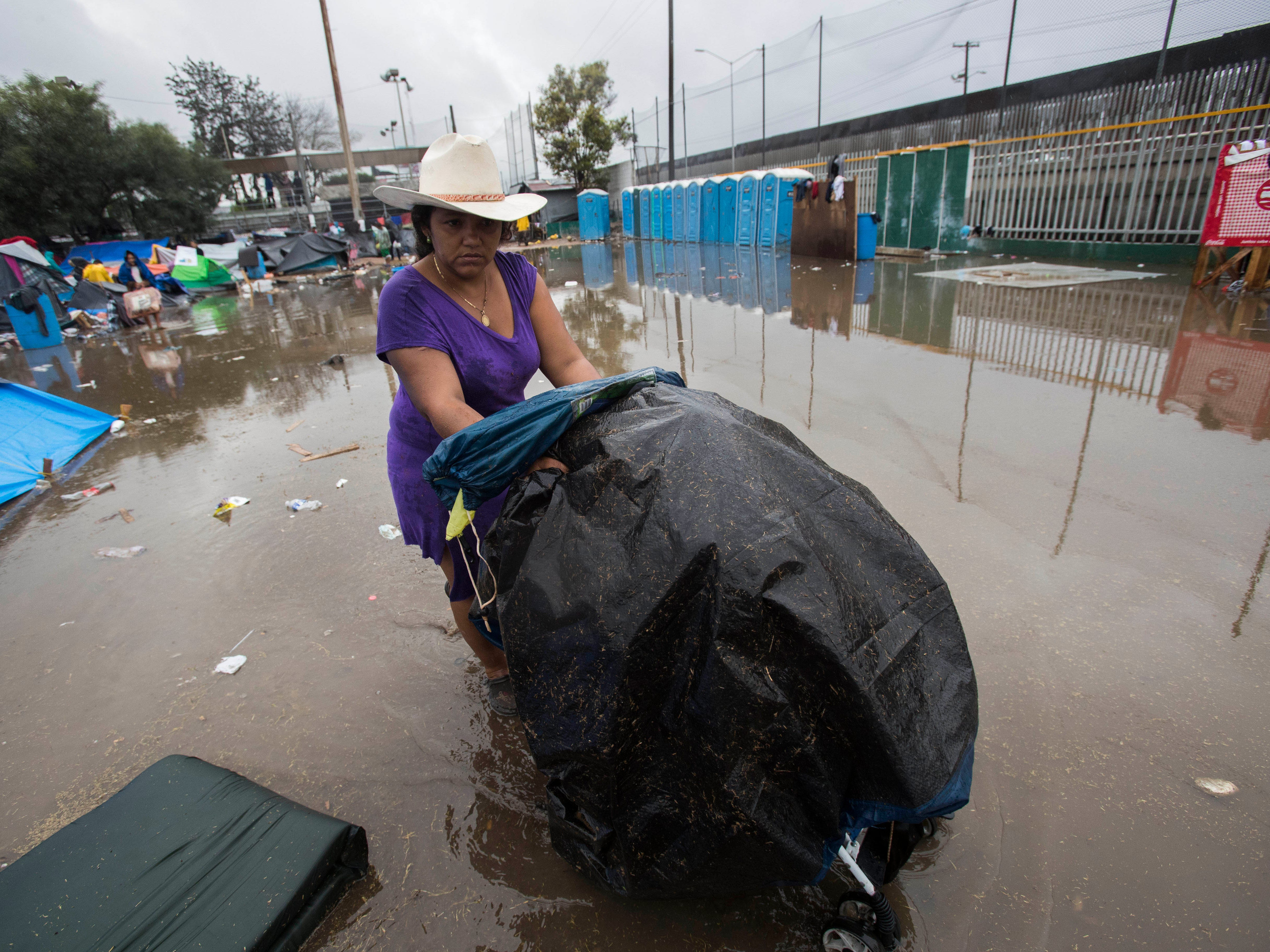 A migrant women carries her belongings through water using a baby carrier at the  Benito Juarez sports complex in Tijuana, Mexico on Nov. 29, 2018.