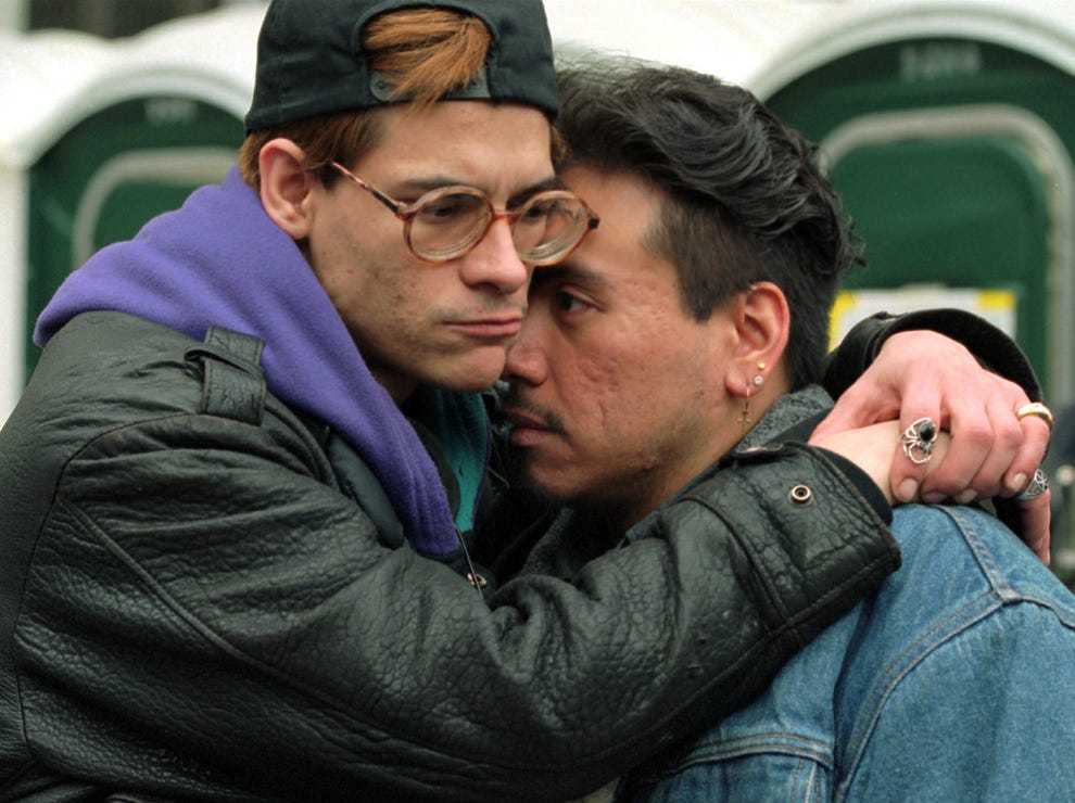 Adam Michael, left, comforts Benito Garcia Delgado in New York's City Hall Park during a 24-hour vigil observing World AIDS Day,  Dec. 1, 1995. The HIV positive couple, who are soon to wed, were listening as the names of thousands of victims of the fatal disease were read aloud.