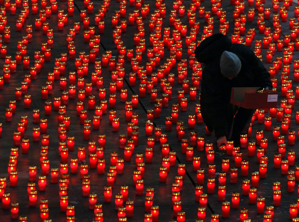 A helper puts up candles in the shape of the African continent in front of the Swiss House of Parliament in Bern, Switzerland, on World AIDS Day 2005. With their action, the relief organization of the Swiss protestant churches wanted to draw the attention to the some 6,000 people who die of Aids each day in Africa.