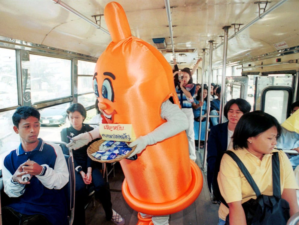 """Condom Man"" passes out free condoms and HIV/AIDS awareness leaflets to bus passengers on Dec. 1, 1999, in Bangkok.  The leaflets and free condoms passed out are part of an HIV/AIDS awareness program in support of World AIDS day."