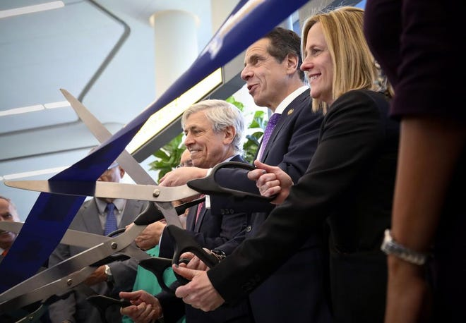 New York's Governor Andrew Cuomo, center, flanked by Rick Cotton, left, executive director of the Port Authority, and Melinda Katz, right, Queens, N.Y. borough president, cut a ribbon to open Terminal B in LaGuardia Airport, as part of ongoing redevelopment at the airport, Thursday Nov. 29, 2018, in New York. (AP Photo/Bebeto Matthews)