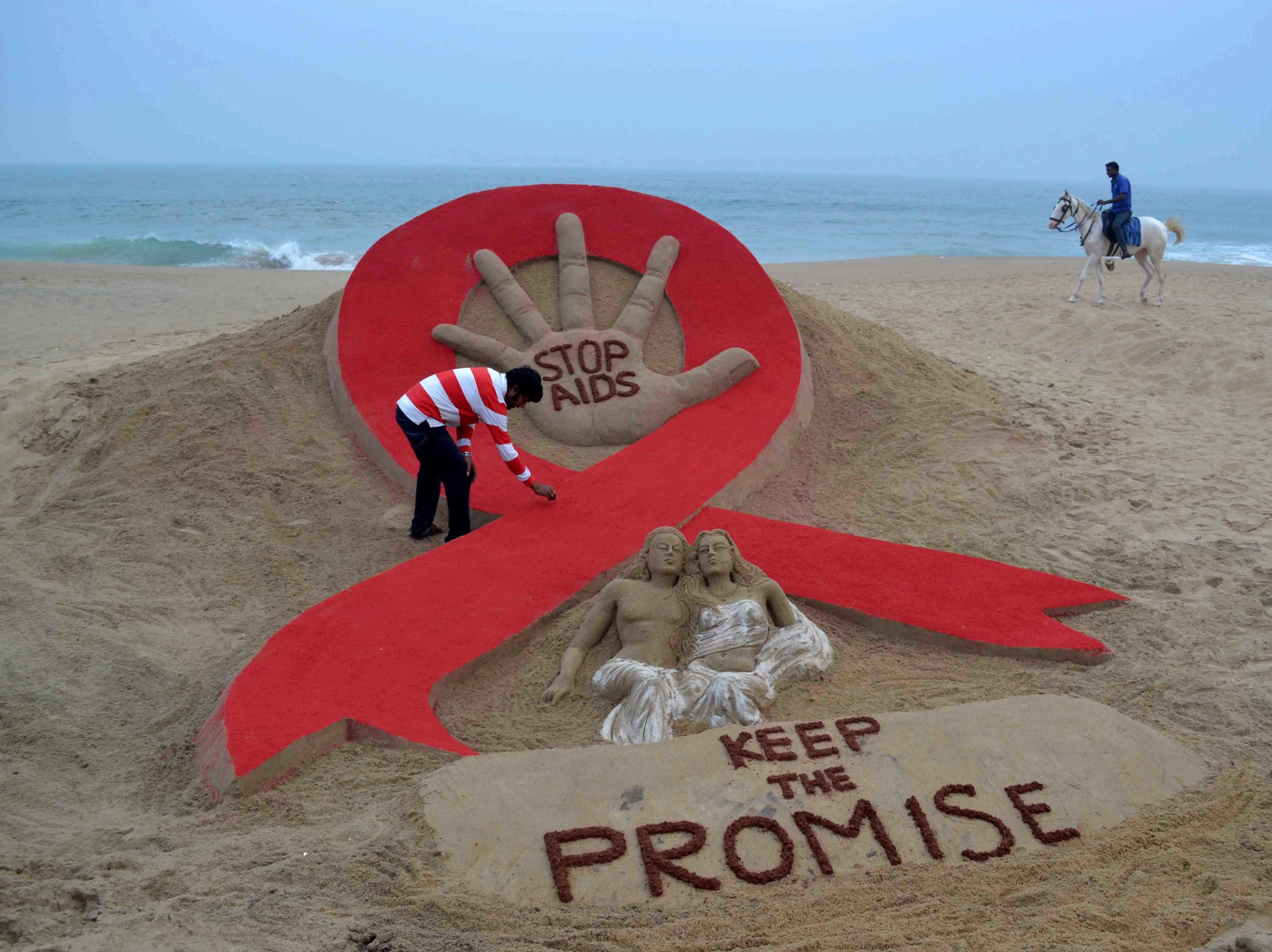 Indian sandartist Sudersan Pattnaik gives the final touches to a sand sculpture on the eve of World AIDS Day, as a horseman rides by on Golden Sea Beach in Puri.