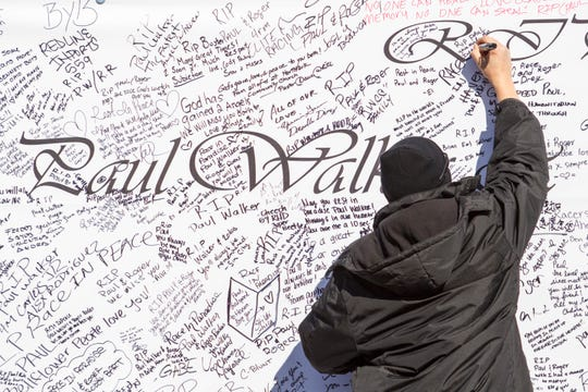 A fan writes messages on a giant poster during a memorial event for Walker in December 2013 in Valencia, California.