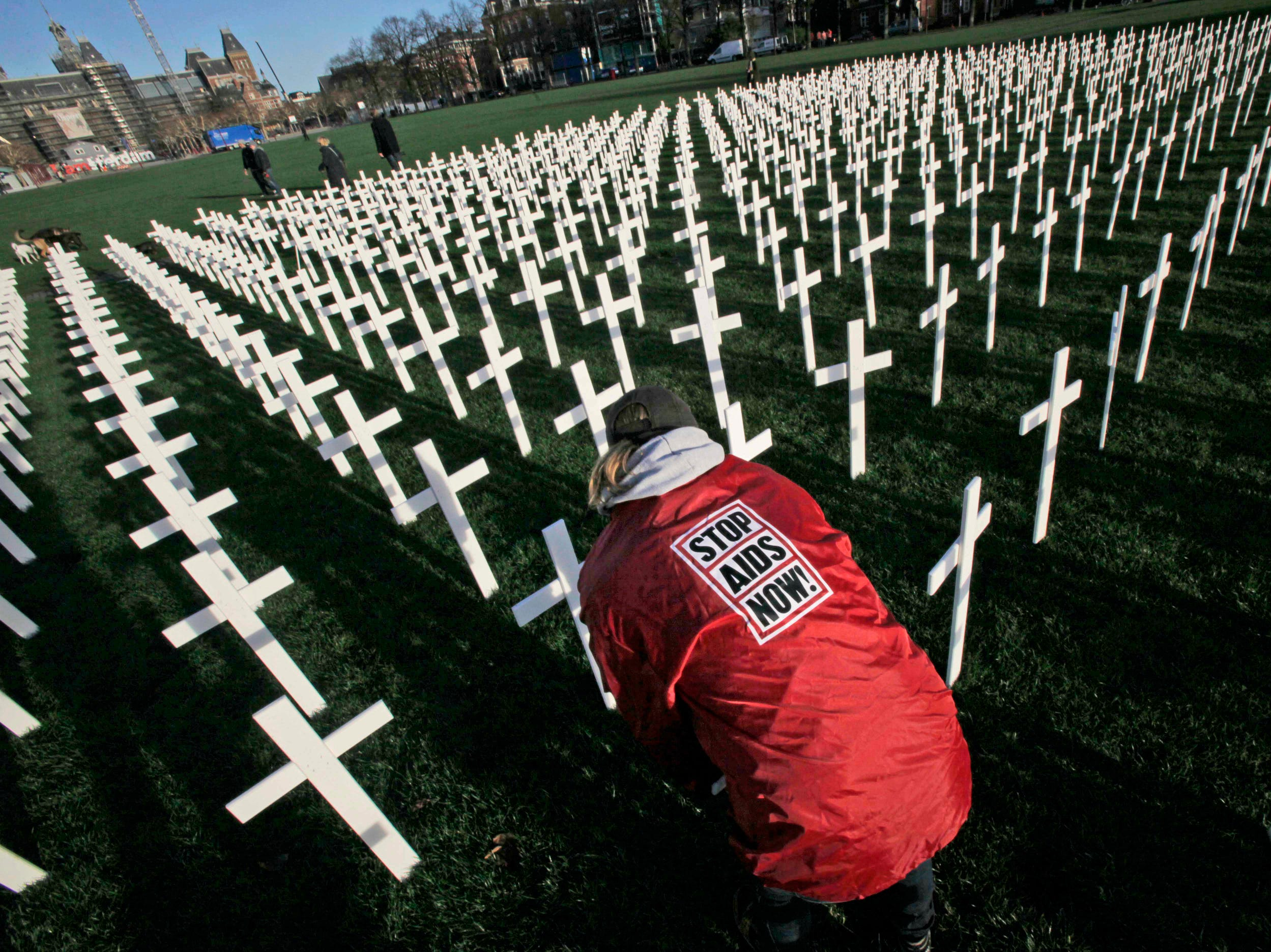 Workers remove the 5,000 crosses which were put on Museum Square to mark World Aids Day in Amsterdam, Netherlands, in 2009. The crosses, planted to look like a cemetery, symbolize the millions of Africans who die of AIDS for lack of access to proper health care and medication.