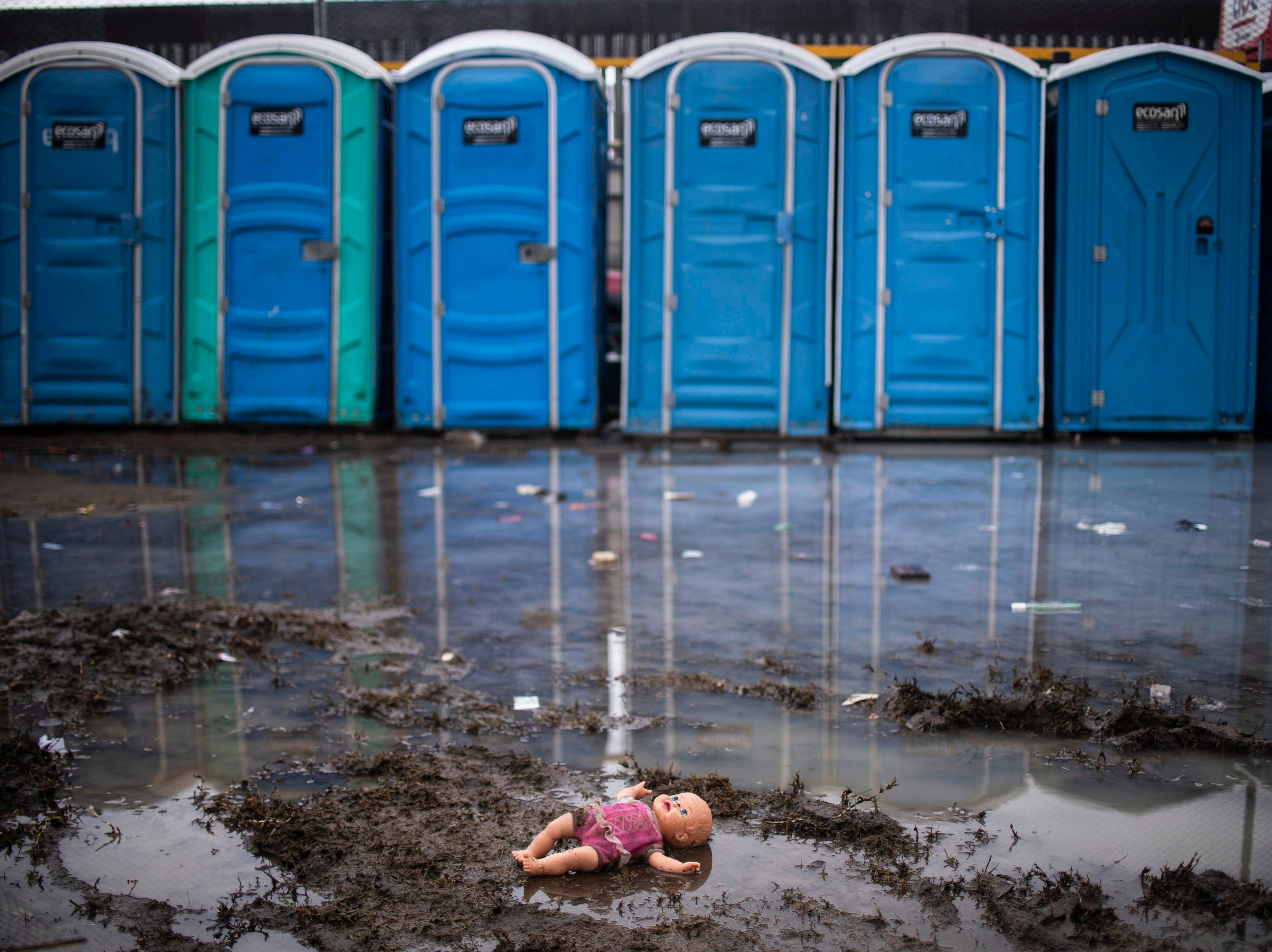 A doll is seen next to chemical toilets at a temporary shelter where Central American migrants trying to reach the US are staying in Tijuana, Baja California State, Mexico, in the border with the US, on Nov. 29, 2018.