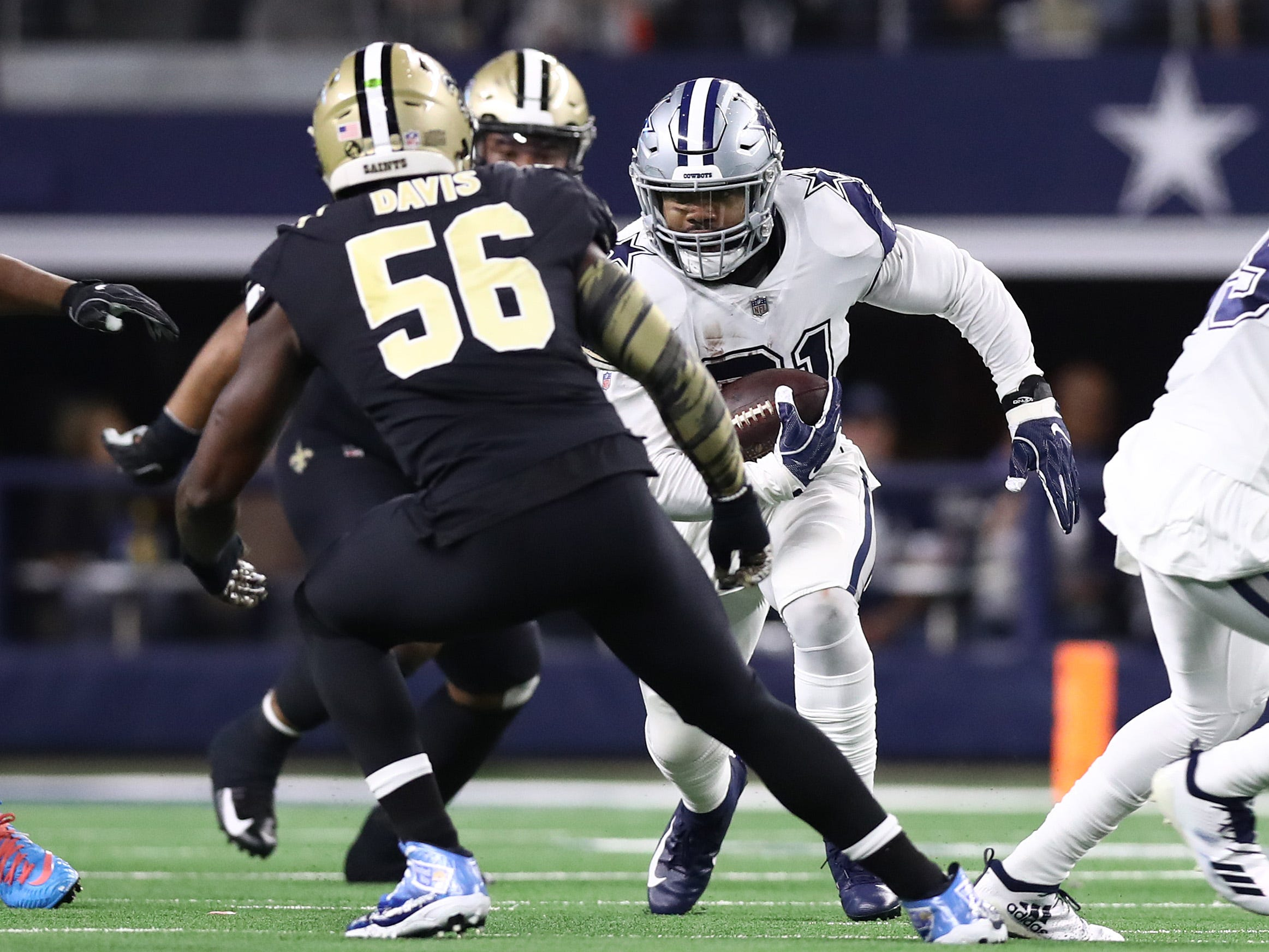 Dallas Cowboys running back Ezekiel Elliott runs with the ball against the New Orleans Saints in the first quarter at AT&T Stadium.