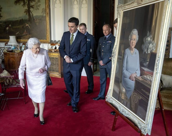 Queen Elizabeth II, accompanied by (L-R) artist Stuart Brown, and RAF leaders, views her new portrait commissioned by the RAF Regiment to celebrate its 75th anniversary, at Windsor Castle on Nov. 30, 2018.