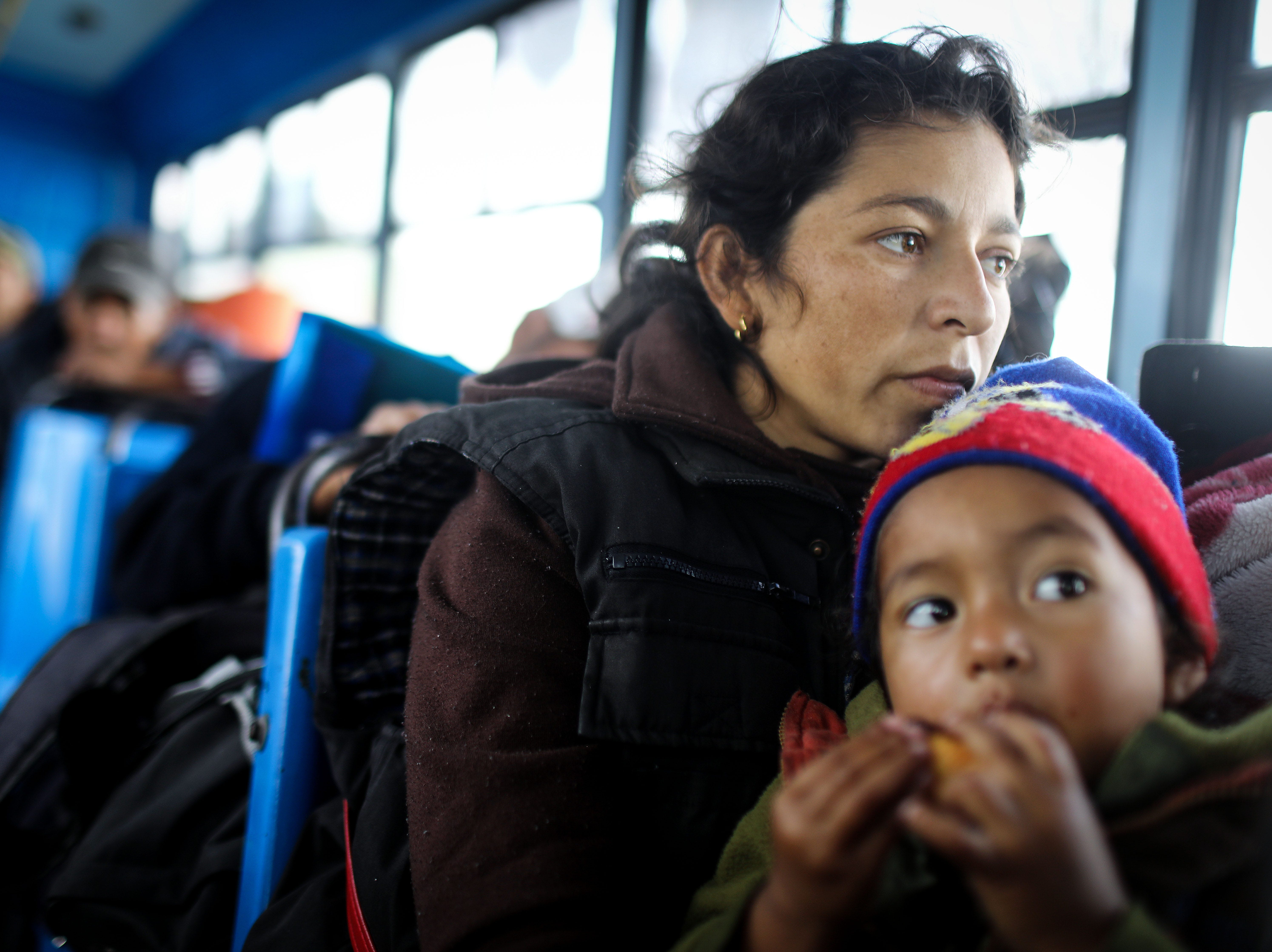 A migrant mother and daughter from Honduras depart on a bus from a temporary shelter where they were staying, on their way to a new shelter on the eastern side of the city, on Nov. 30, 2018 in Tijuana, Mexico.