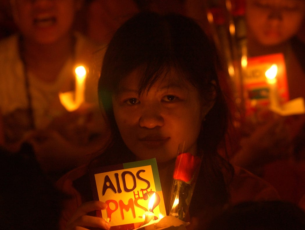 "An Indonesian student holds a candle and a sign during a rally to mark World AIDS Day in Jakarta, Indonesia, Dec. 1, 2005.  Indonesia's response to an emerging AIDS epidemic is ""inadequate,"" the head of the U.N. agency fighting the virus said Wednesday, calling on the president to take a more active role. ""PMS"" is an Indonesian acronym for sexually-transmitted disease."