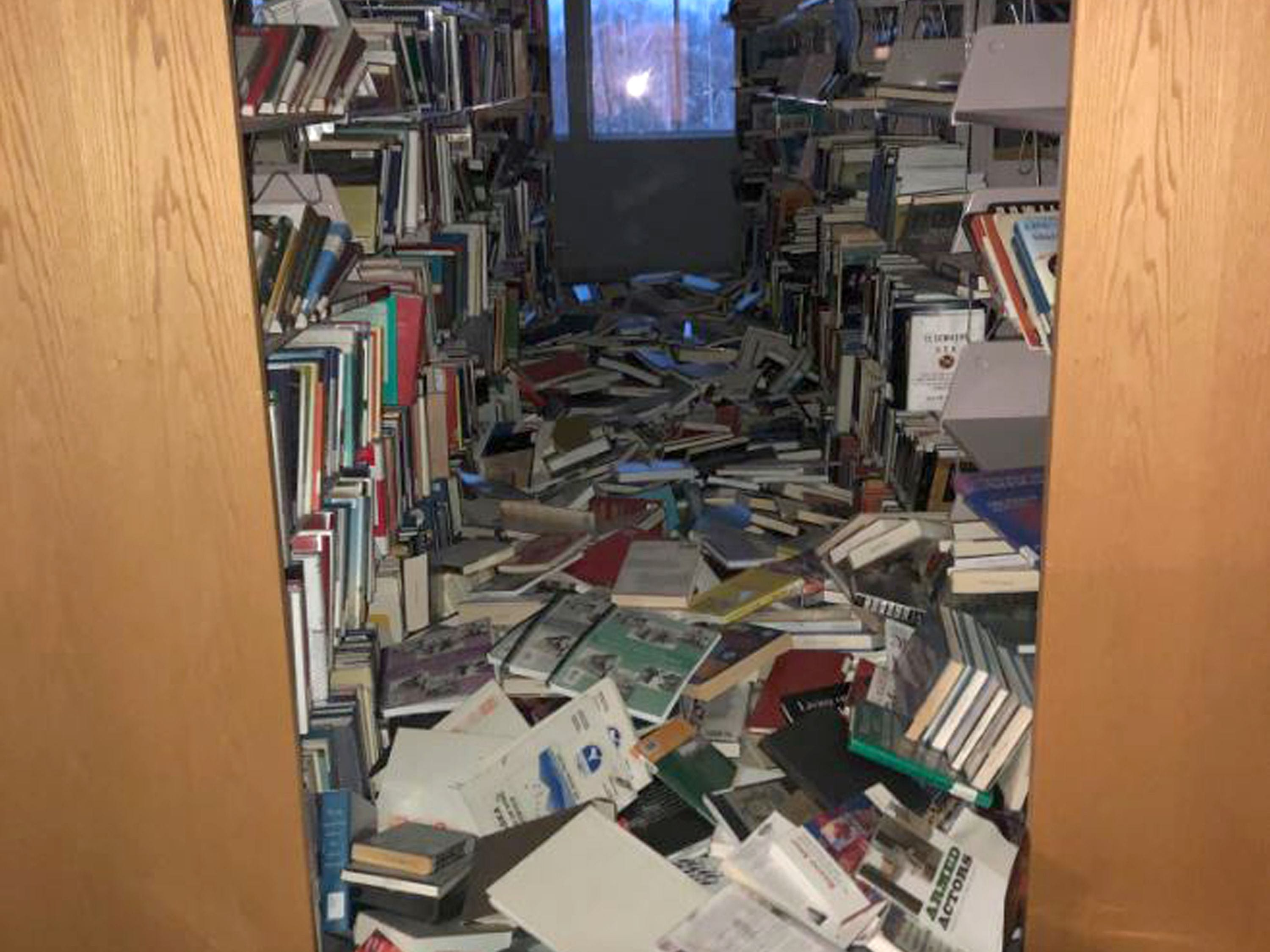 In this image courtesy of Dr. Holly A. Bell, books and ceiling tiles litter the floor at the The Mat-Su College library in Anchorage, Alaska, on Nov. 30, 2018, after a 7.0 magnitude earthquake. The powerful earthquake caused damage to homes and businesses and triggering a tsunami warning. The earthquake was located about eight miles north of Anchorage and struck at 8:29 am local time, the US Geological Survey said.