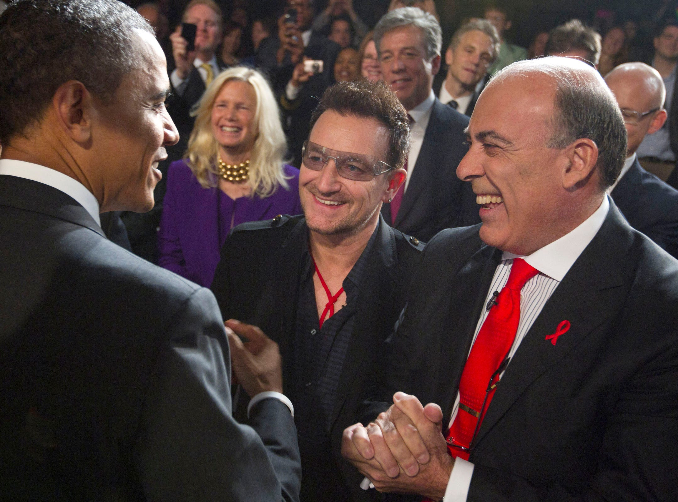 President Barack Obama greets U2 front man Bono, center, and Muhtar Kent, chairman of the Board and chief executive officer of The Coca-Cola Company, right, after speaking during a World AIDS Day event at George Washington University in Washington, in 2011.