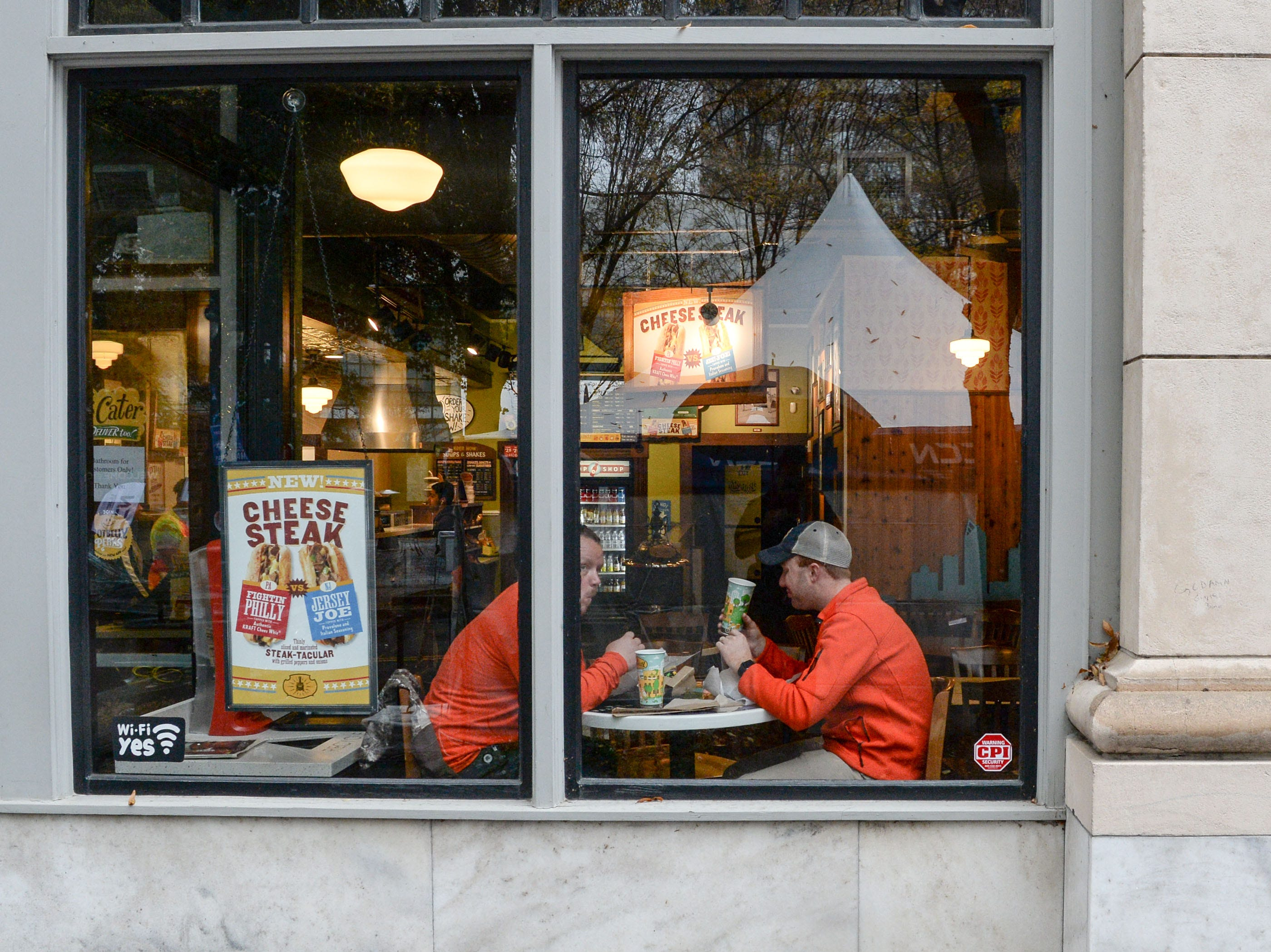 Clemson fans stop to eat inside the Potbelly Sandwich shop at the ACC Fan Fest in downtown Charlotte on Saturday, December 1, 2018.
