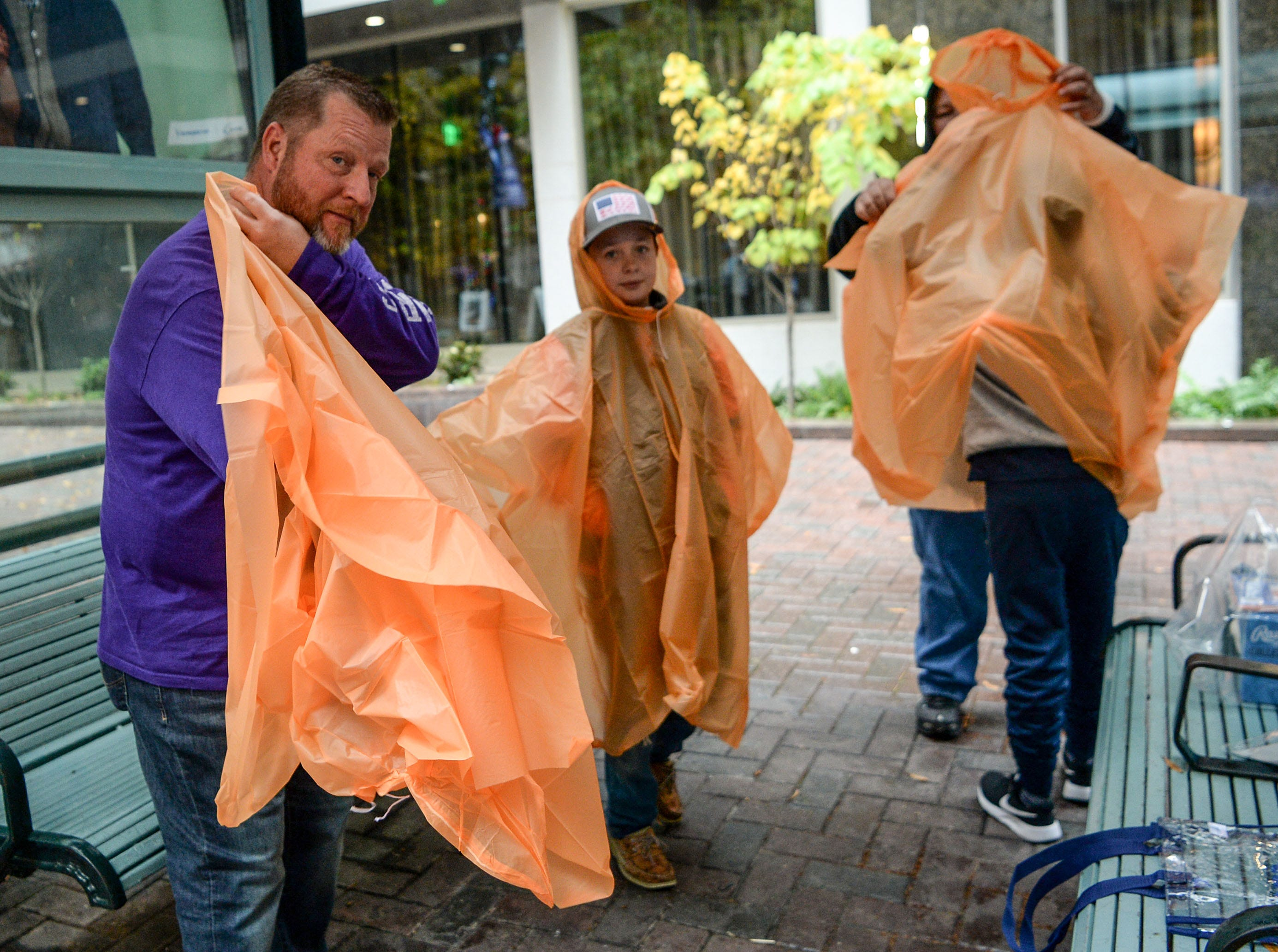 Clemson fan Jamie Suggs of Loris, left, puts on a poncho near his son Jay Suggs, middle, at the ACC Fan Fest in downtown Charlotte on Saturday, December 1, 2018.