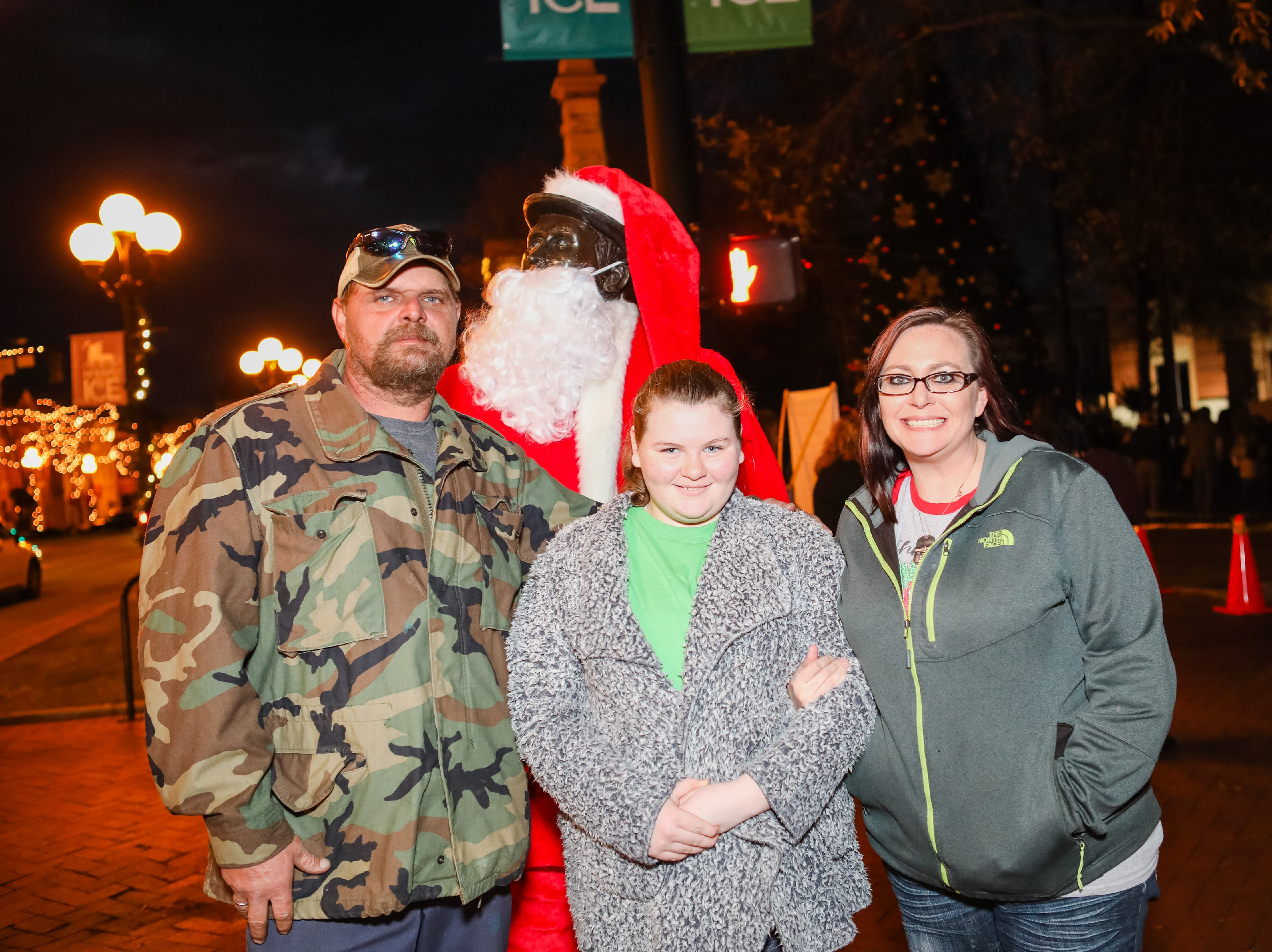 John Browing , Ashley Browing, and Macy Haynes pose infant of Santa during the Piedmont Natural Gas Holiday Walk and Christmas Tree Lighting in downtown Anderson