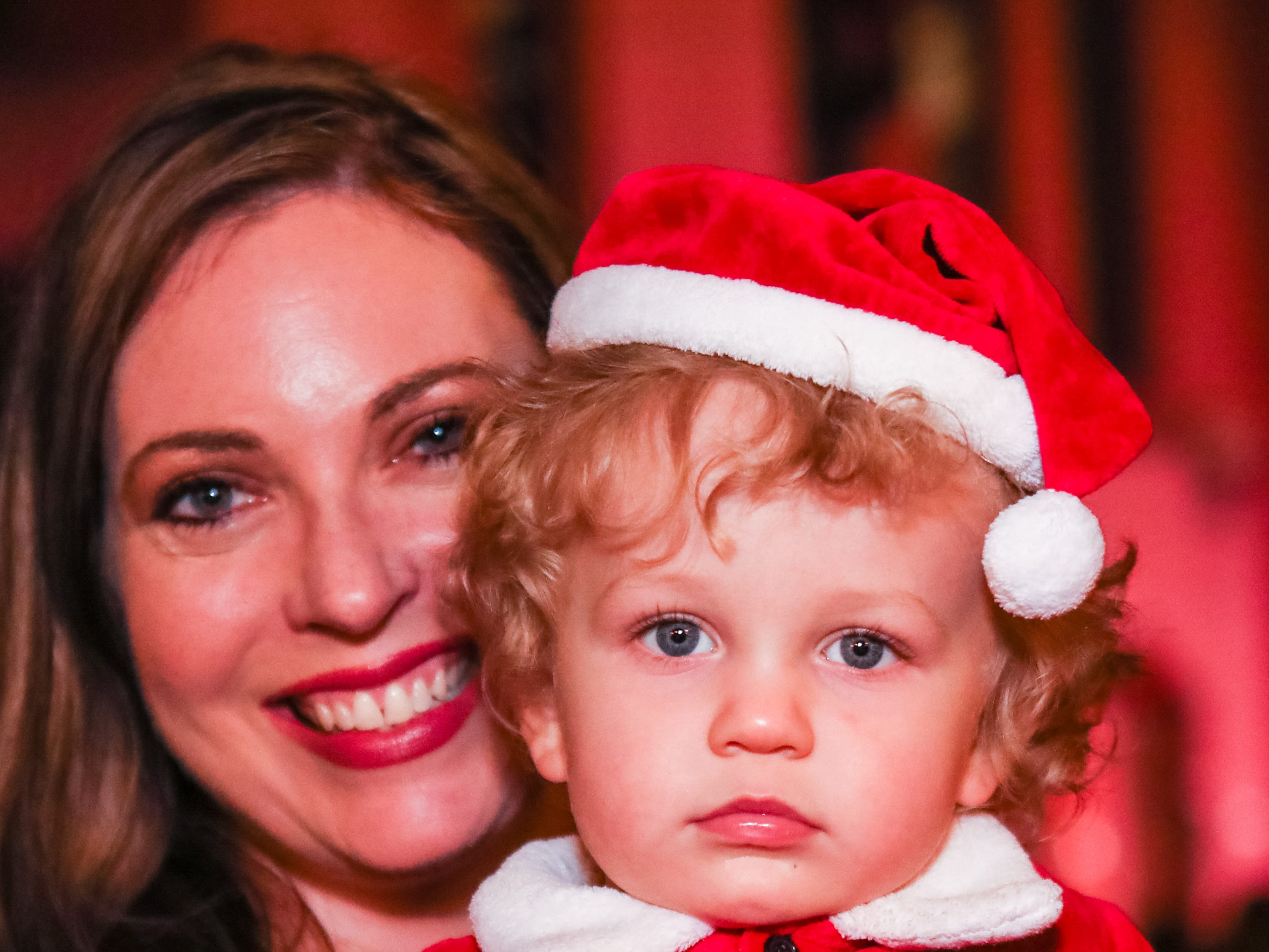Cole Szmurio  (20 months) and his Breann Szmurio  enjoy the festivities at the  Piedmont Natural Gas Holiday Walk and Christmas Tree Lighting in downtown Anderson