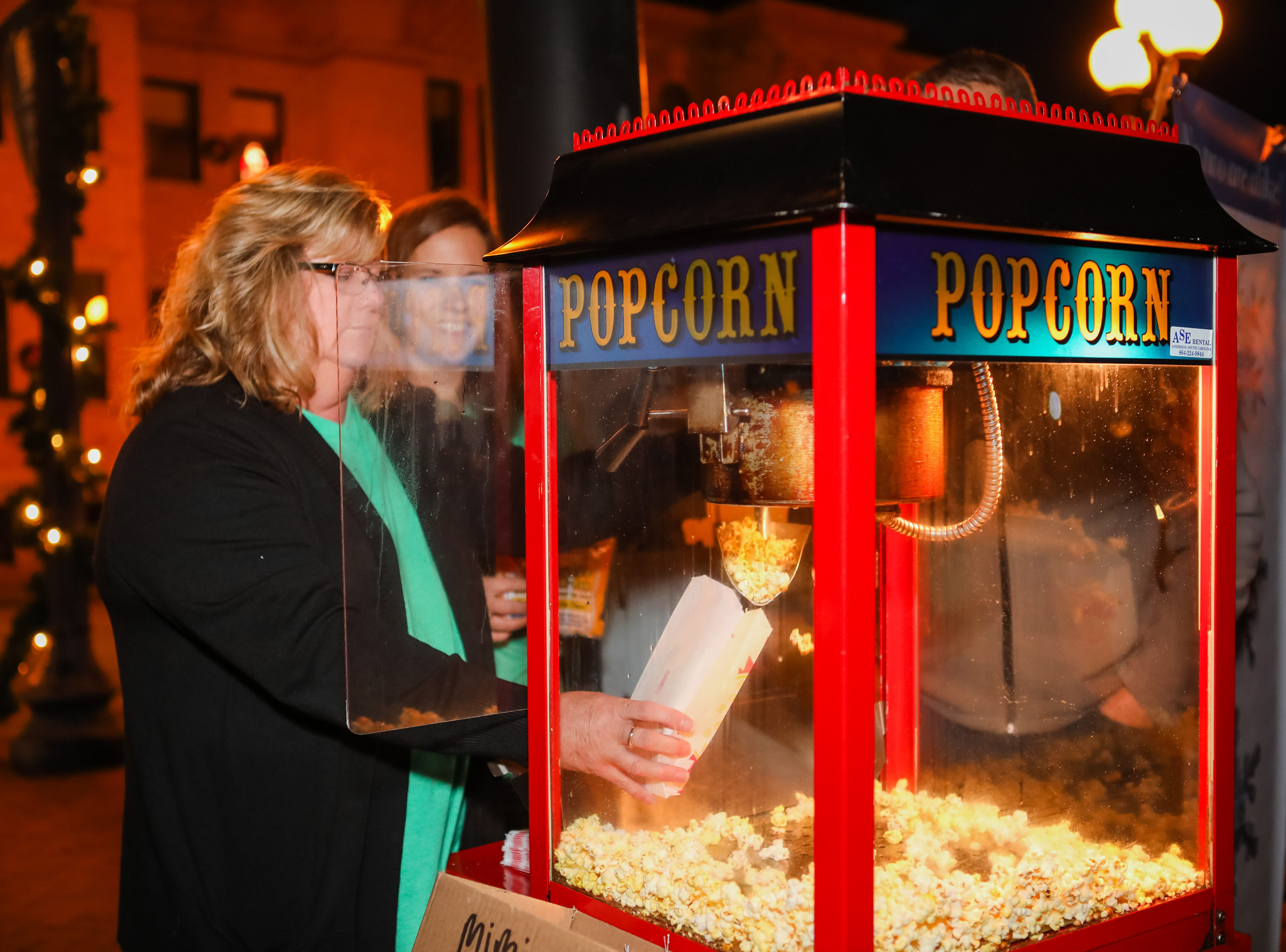 Kari Brown hands out popcorn during the Piedmont Natural Gas Holiday Walk and Christmas Tree Lighting in downtown Anderson