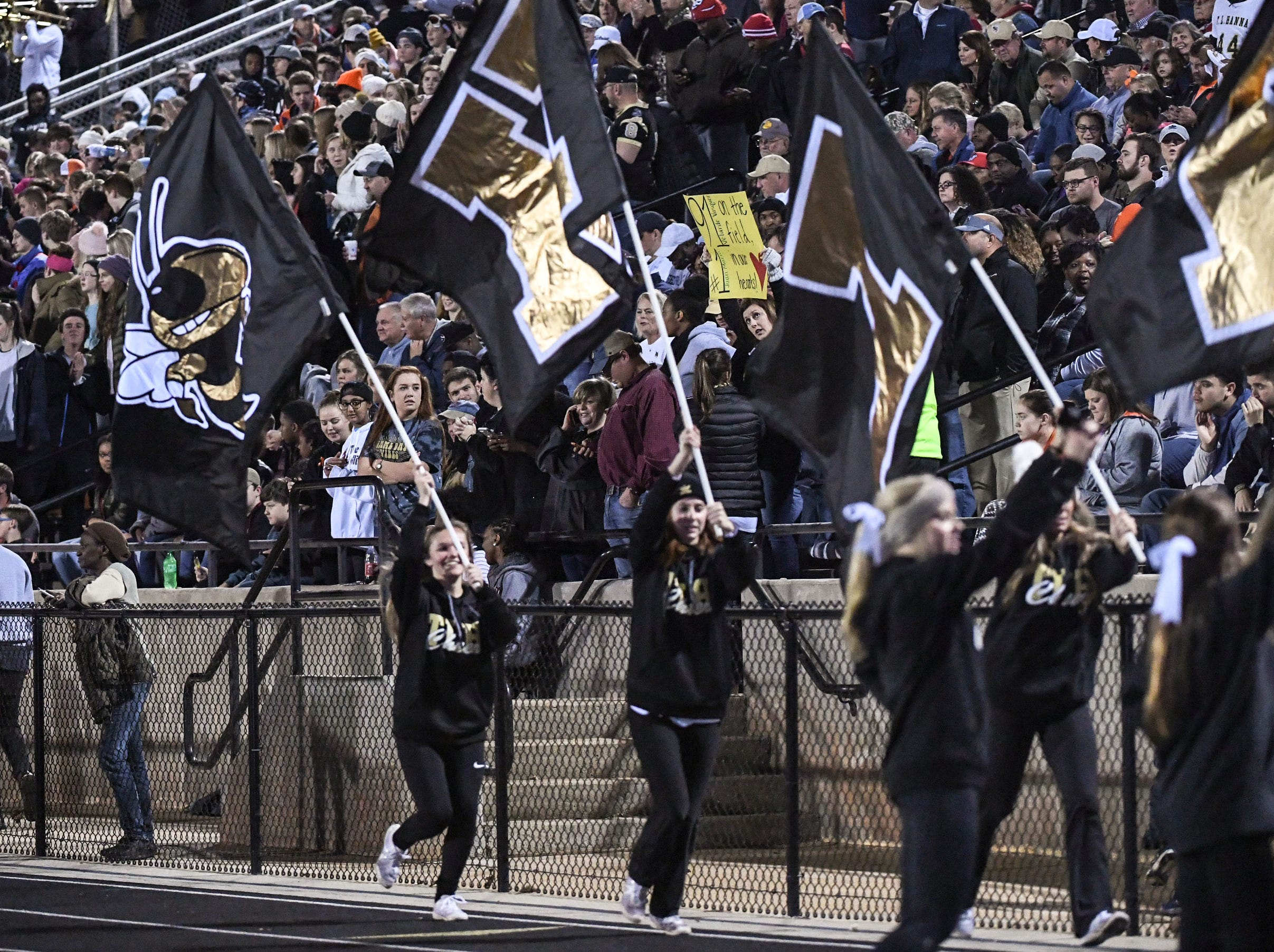 TL Hanna High School cheerleaders carry flags during the first quarter of the Class AAAAA state playoffs at TL Hanna High School in Anderson on Friday, November 30, 2018.
