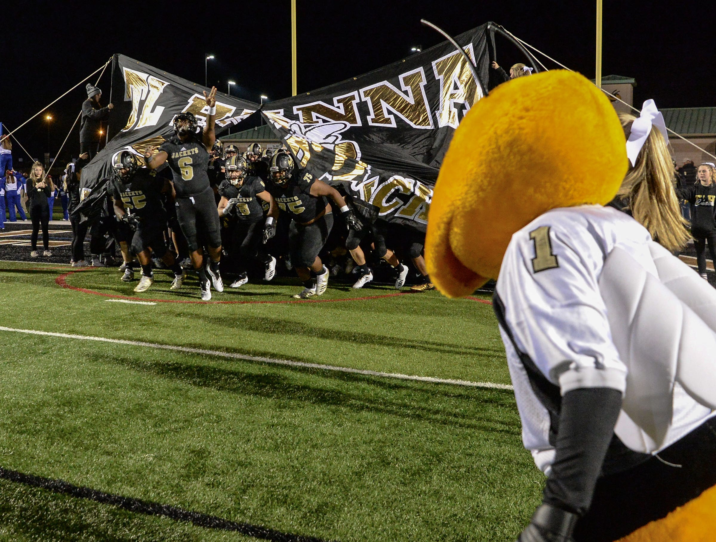 TL Hanna High School players break through a banner before the kickoff with Byrnes in the Class AAAAA state playoffs at TL Hanna High School in Anderson on Friday, November 30, 2018.