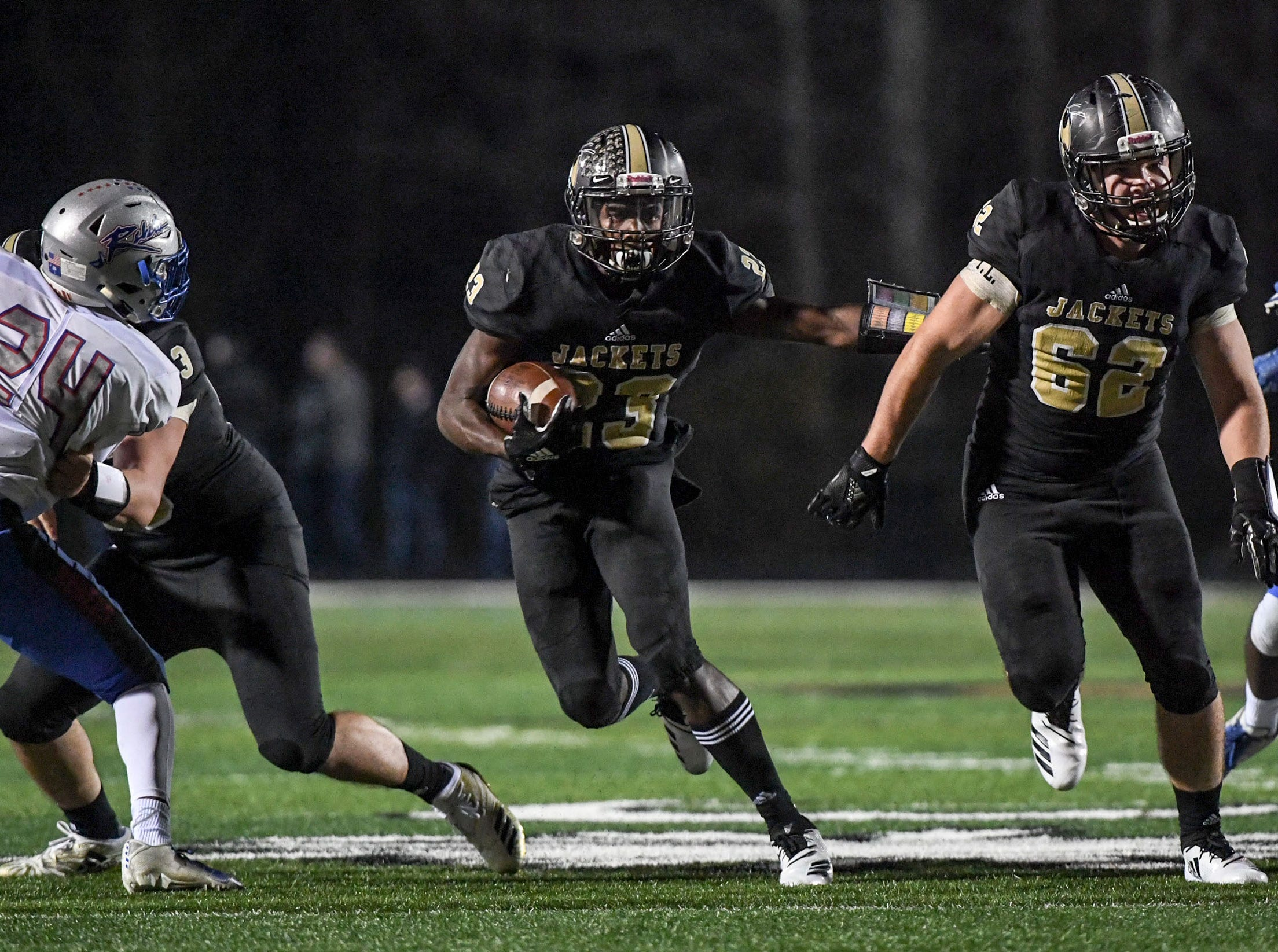 TL Hanna senior Isaiah Norris (23) runs near TL Hanna senior Mac Malone (62) during the first quarter of the Class AAAAA state playoffs at TL Hanna High School in Anderson on Friday, November 30, 2018.