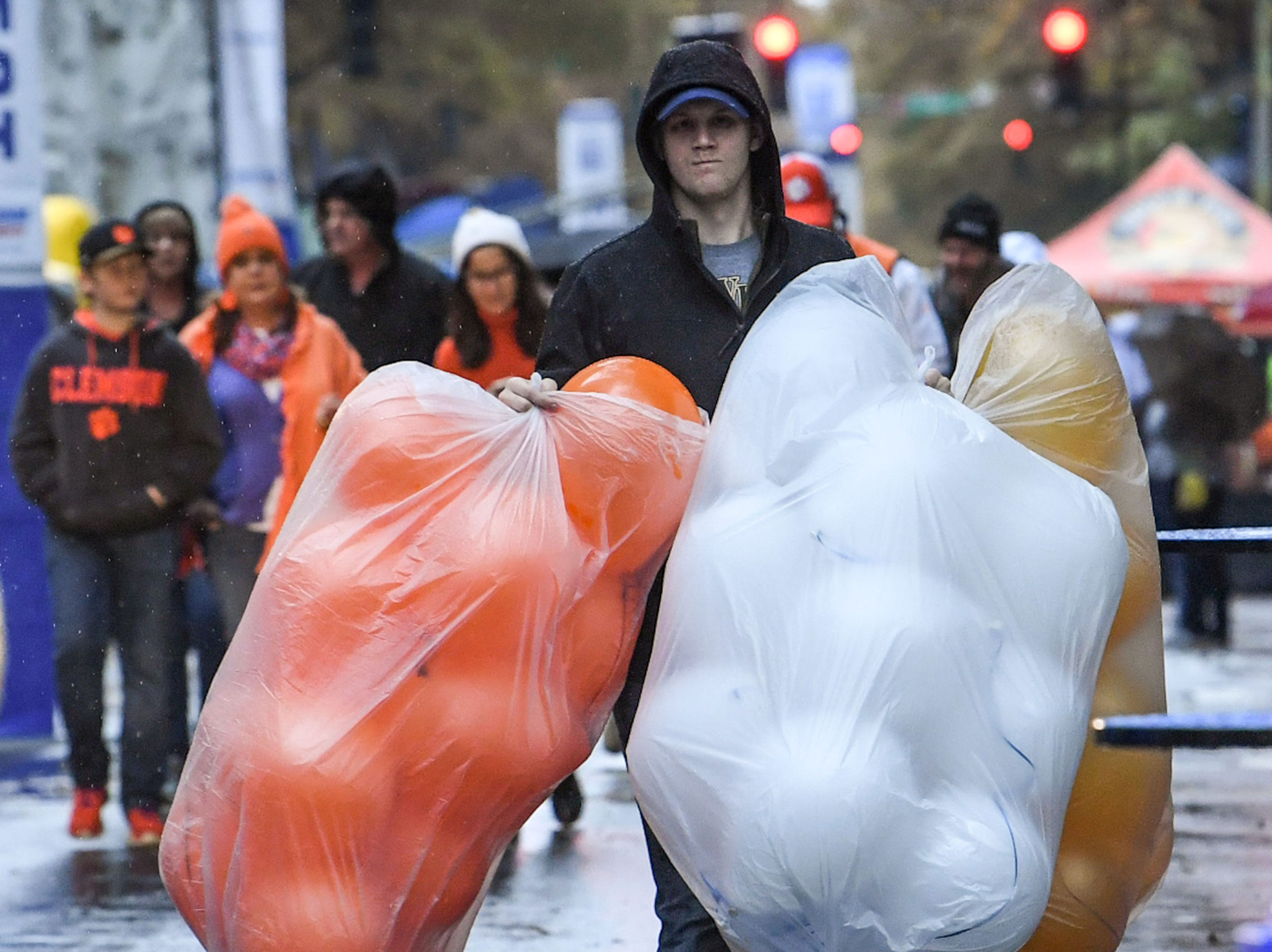 Josh Strickland carries balloons representing Clemson and Pitt for a hospitality booth at the ACC Fan Fest in downtown Charlotte on Saturday, December 1, 2018.