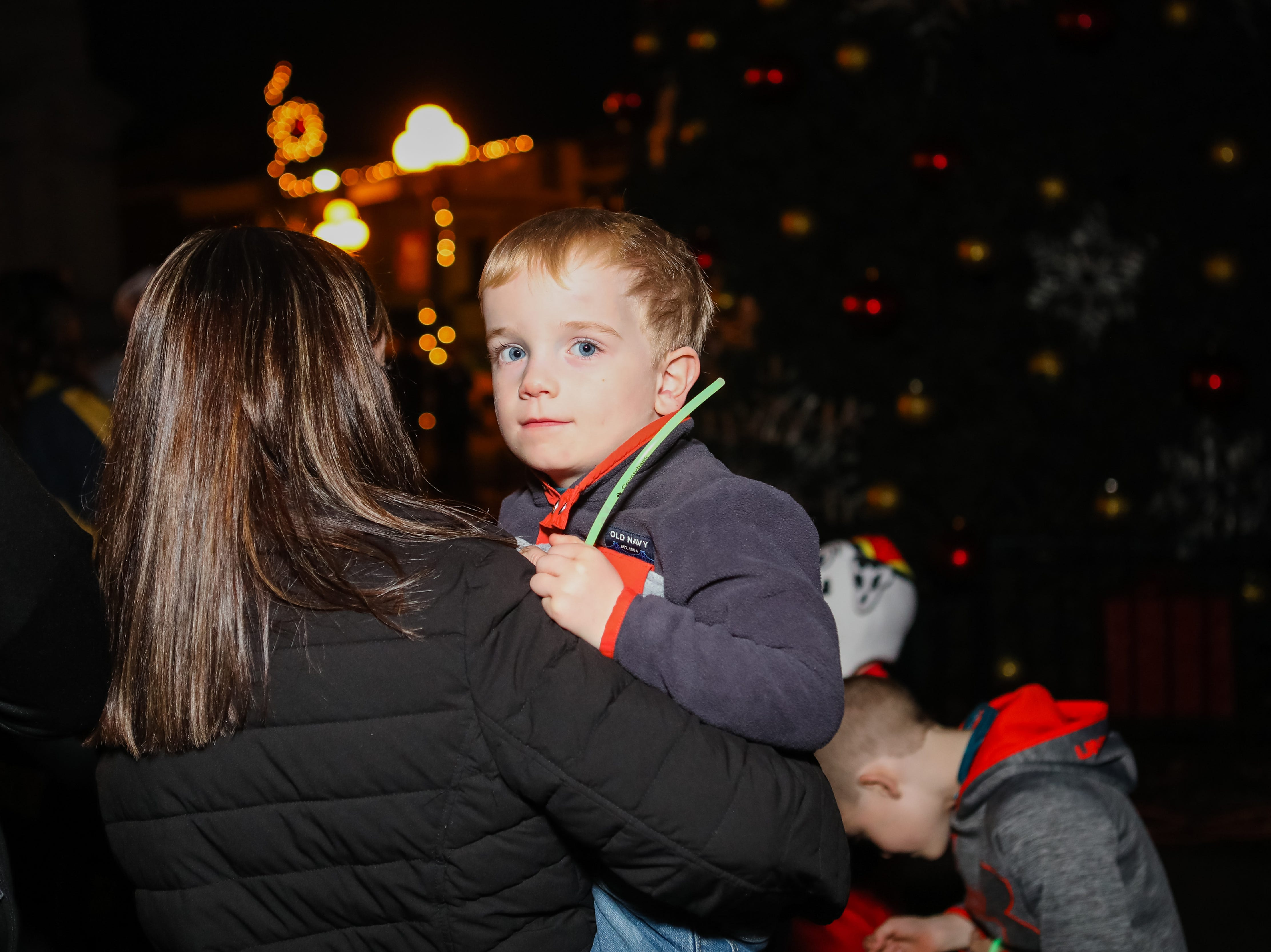 Three year old Chase Chapman plays with his glow stick at the Piedmont Natural Gas Holiday Walk and Christmas Tree Lighting in downtown Anderson