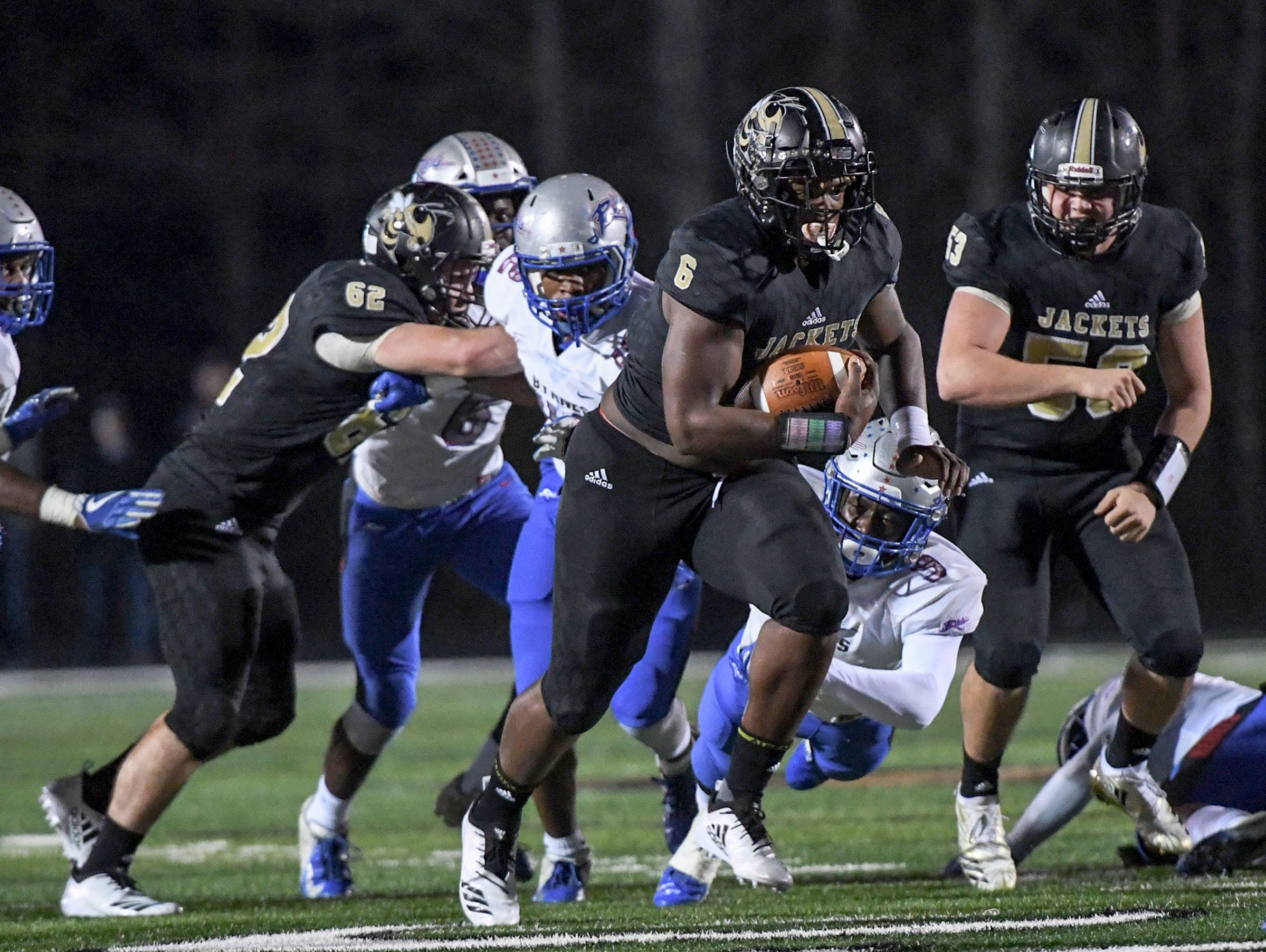 TL Hanna senior Zacch Pickens (6) runs near linemen TL Hanna senior Mac Malone (62) and TL Hanna junior Raymond Fretwell (53) during the first quarter of the Class AAAAA state playoffs against Byrnes High School at TL Hanna High School in Anderson on Friday, November 30, 2018.