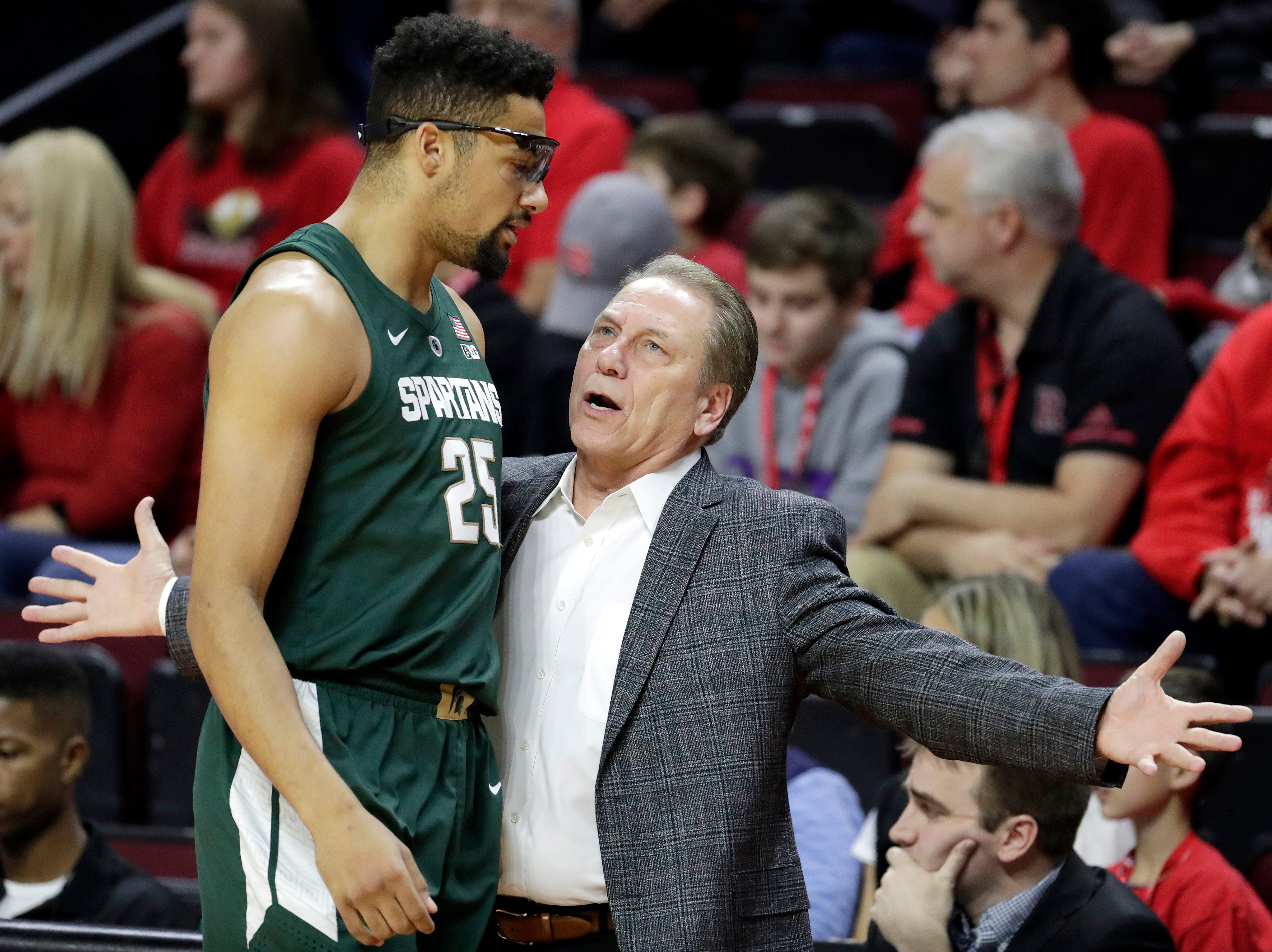 Michigan State head coach Tom Izzo, right, talks to forward Kenny Goins (25) during the first half of an NCAA college basketball game against Rutgers, Friday, Nov. 30, 2018, in Piscataway, N.J. (AP Photo/Julio Cortez)