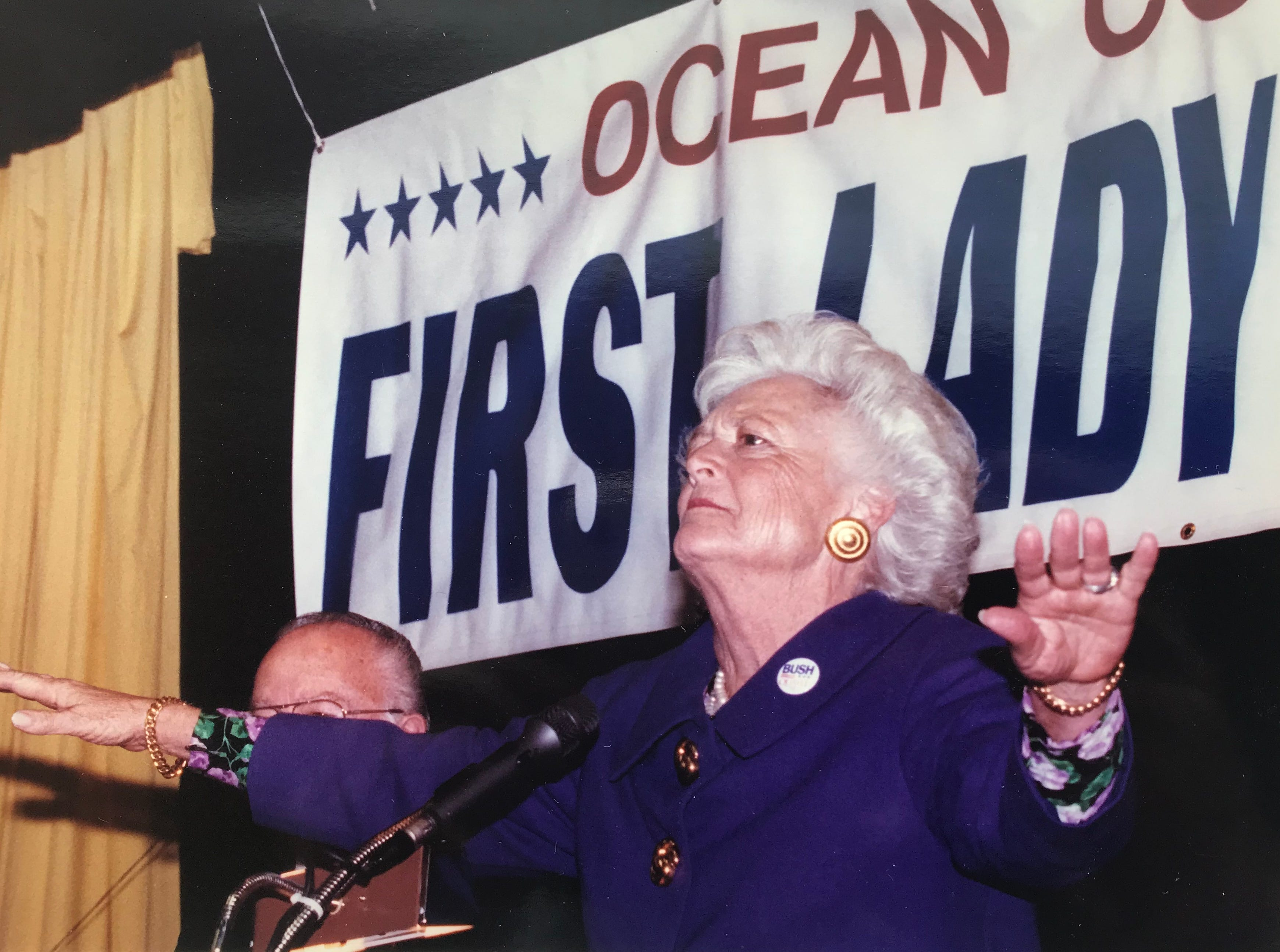 First Lady Barbara Bush tries to quiet the crowd gathered at the Leisure Village East Clubhouse in Lakewood on Oct. 30, 1992.
