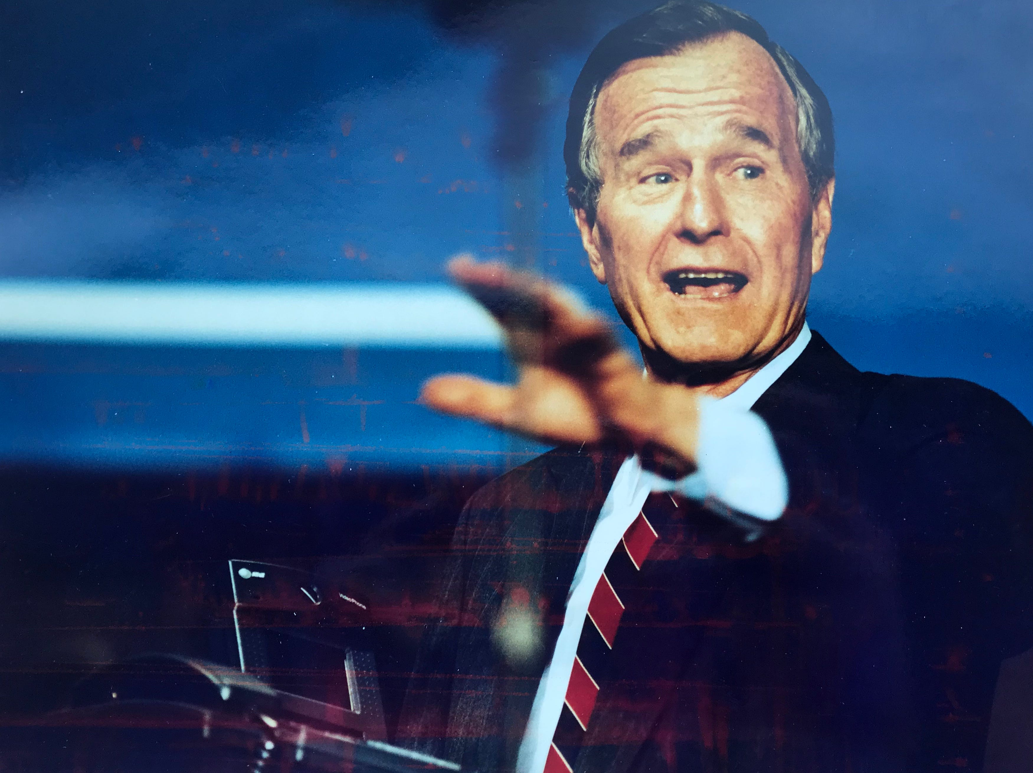President George H.W. Bush waves to the crown at AT&T in Basking Ridge after receiving a new video phone.
