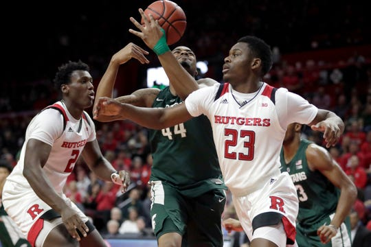 Michigan State forward Nick Ward (44) collects a rebound while Rutgers guard Montez Mathis (23) and center Shaquille Doorson (2) attack.