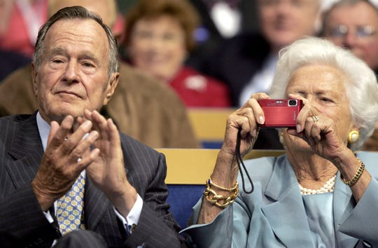 Former President George H. W. Bush applauds while his wife Barbara snaps a photo at the Xcel Energy Center in St. Paul, MN, during the second session of the Republican National Convention in 2008.