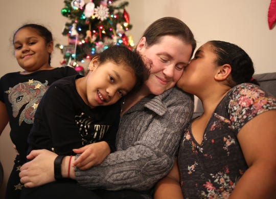9-year-old Keira Canada kisses her mother Jessica Canada with her sisters Amaya (left) and Isabella (center) joinin in at their Jackson home. Keira recently called 9-1-1 while her mom was having a seizure.