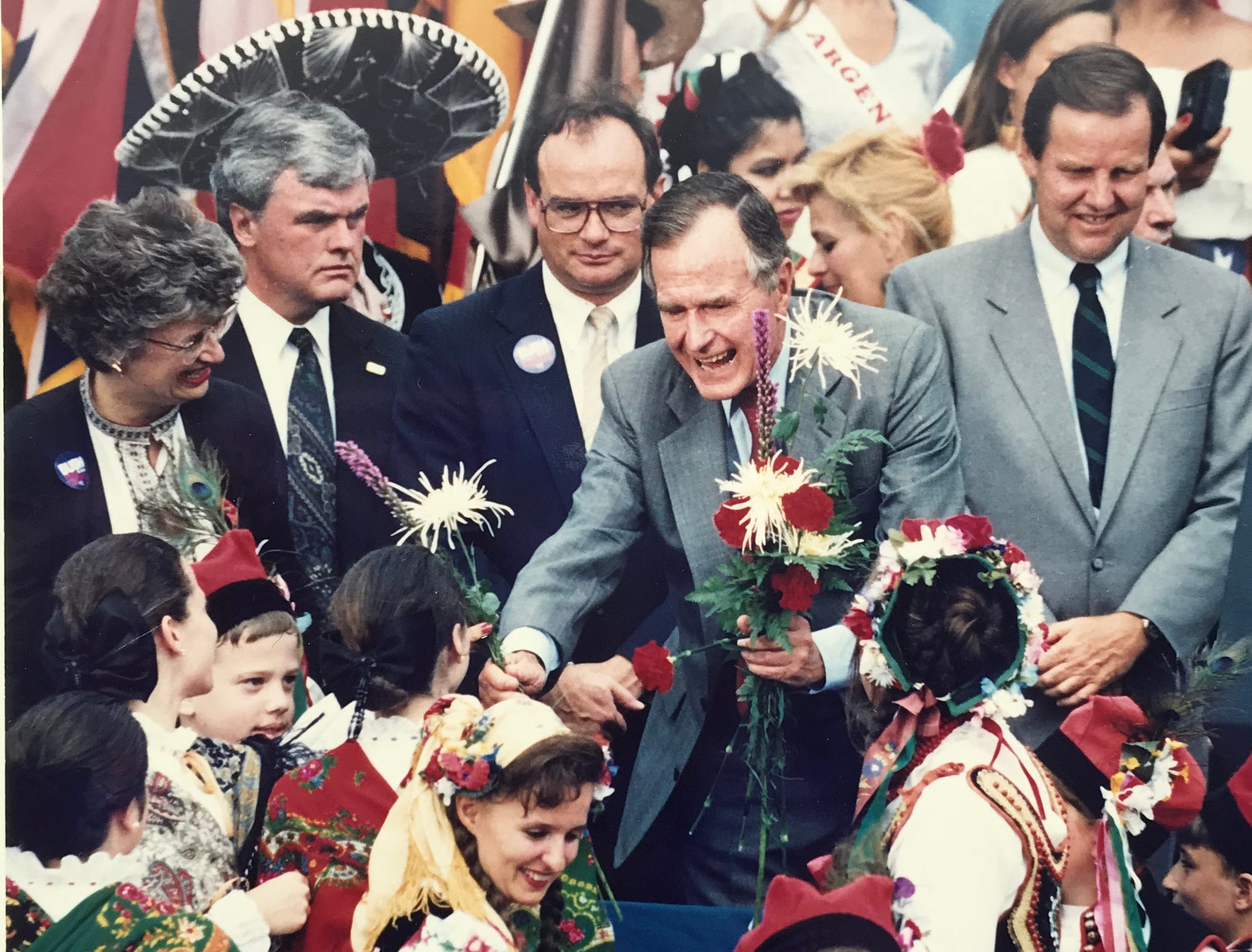 President George H.W. Bush receives flowers from children from the Polish National Alliance outside Three Saints Russian Orthodox Church in Garfield on July 21, 1992. Behind him are former state Sen. Leanna Brown, Senate President Donald DiFrancesco, and Gov. Thomas H. Kean.