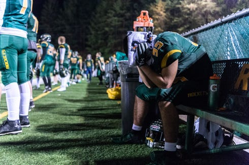 Reynolds' Cody Creasman holds his head because of a concussion he suffered during the game moments before their loss to Mount Tabor in their third round playoff game Nov. 30, 2018.