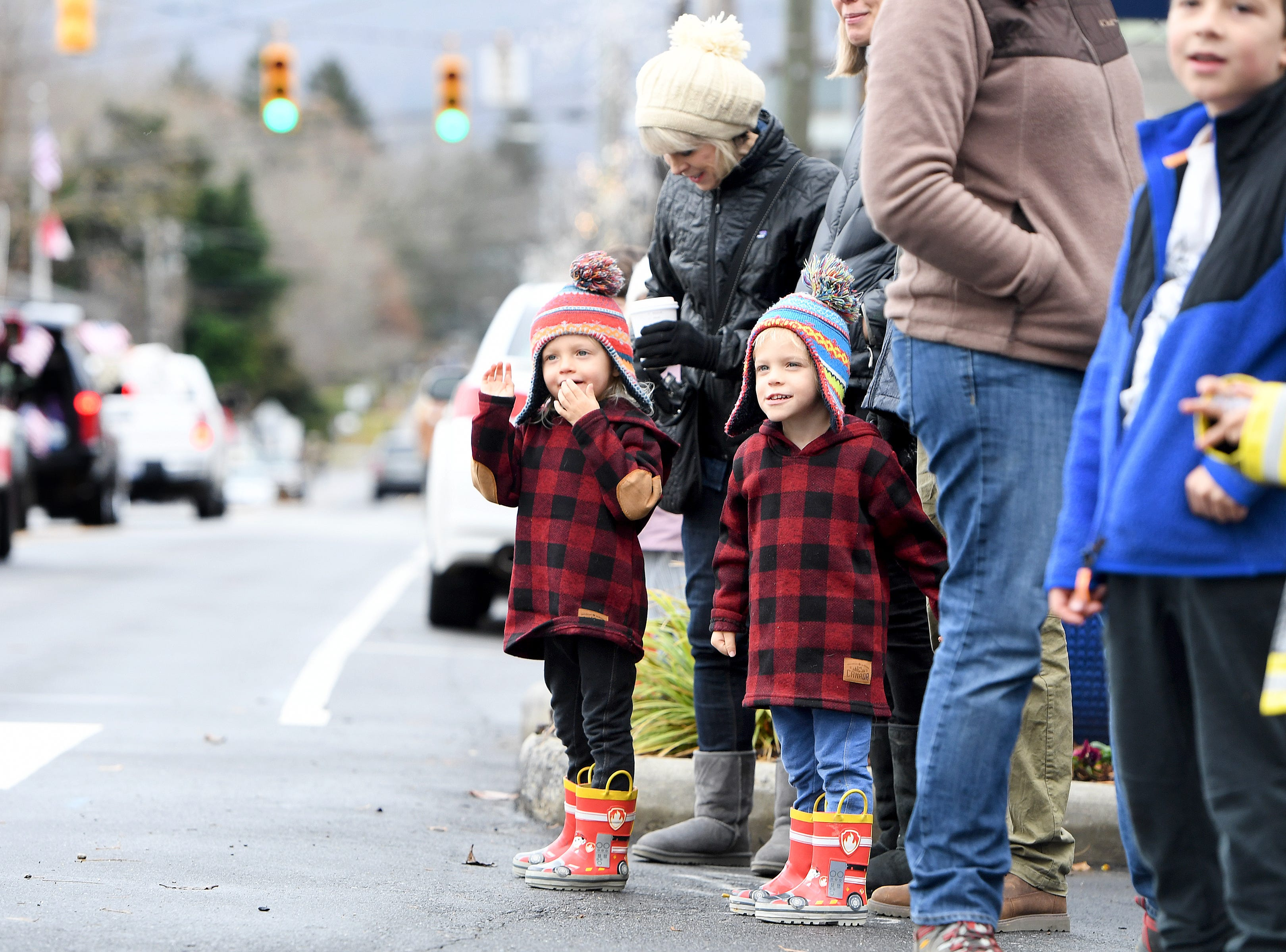 Three-year-old twins Harry, left, and Benny Eichelman wave to people in vehicles as they parade down Main Street in the Weaverville Christmas Parade on Dec. 1, 2018.