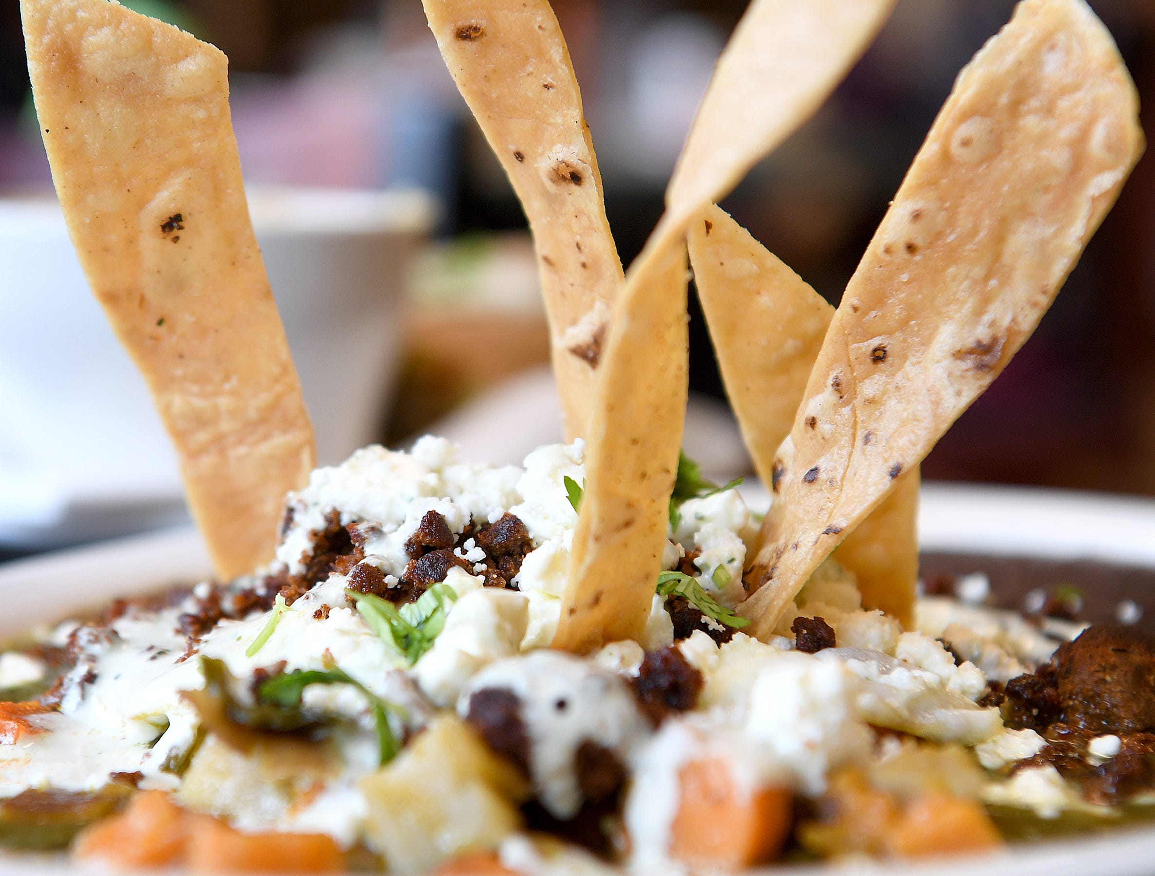 The huevos rancheros at Abeja's House Cafe is two eggs served on top of tomatillo salsa, roasted potatoes and refried Mexican black beans topped with Mexican chorizo sausage, feta cheese, avocado cream sauce, and gluten free corn tortilla strips.